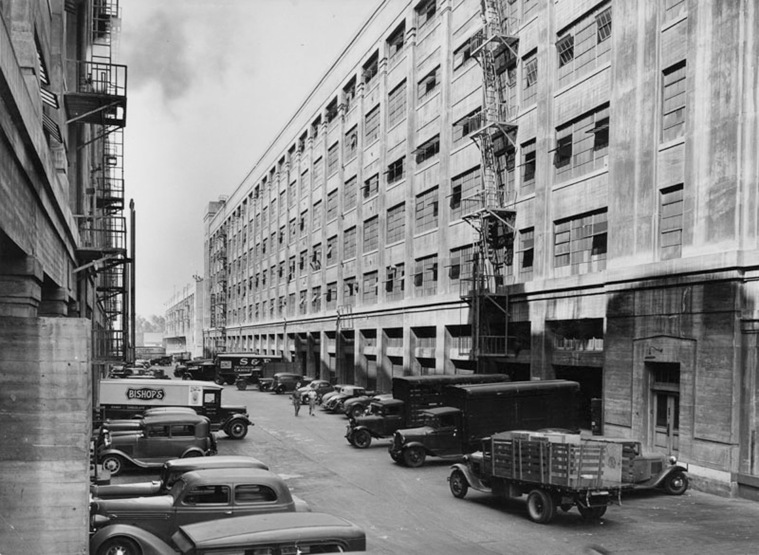 black and white photo of old trucks lined in front of an old building