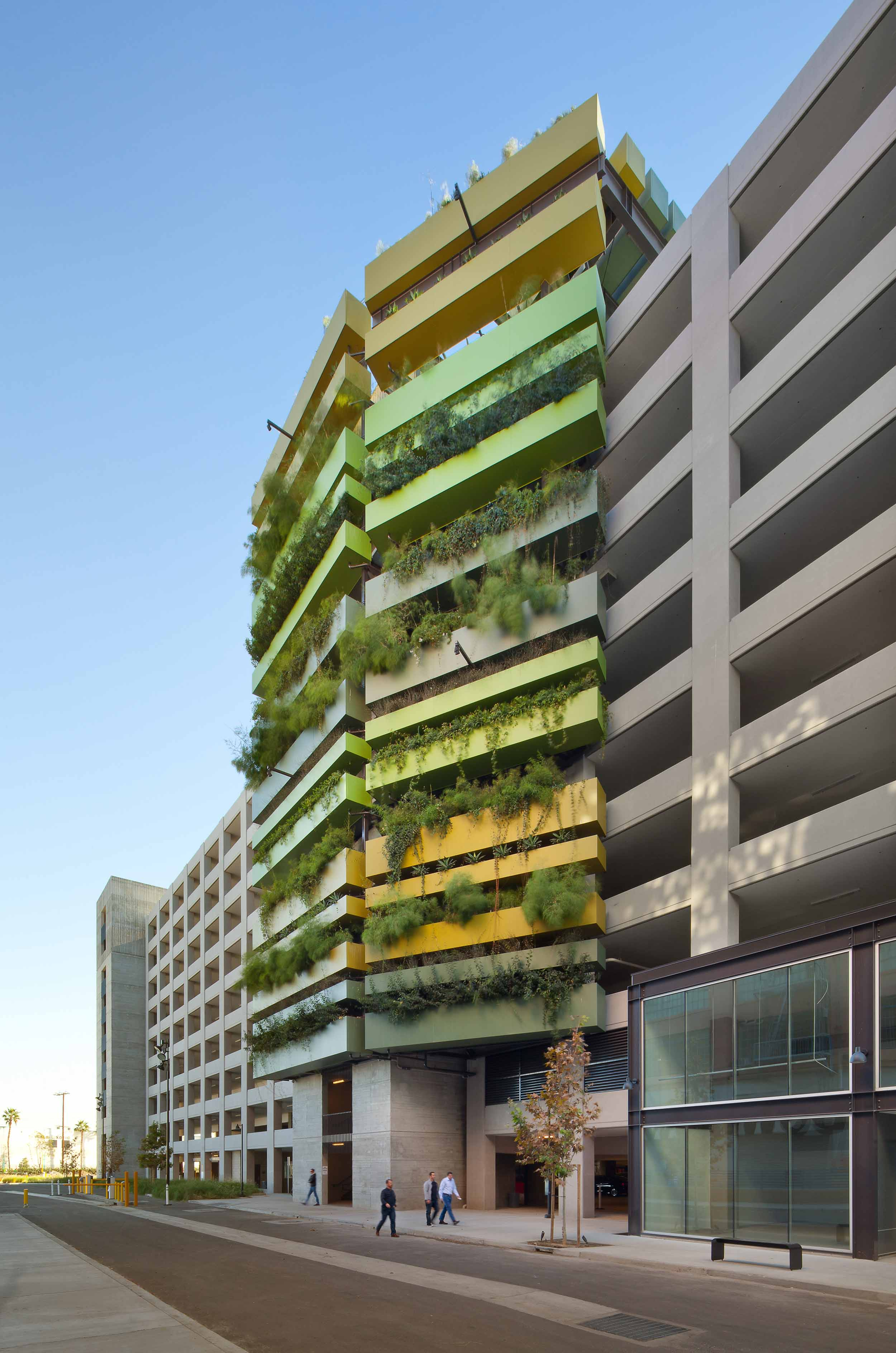 exterior shot of a garage with a green facade and plants cascading down