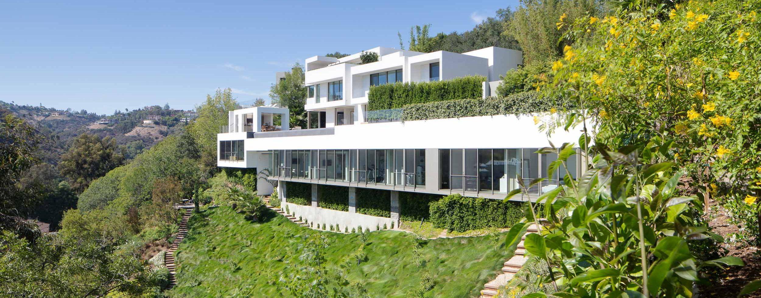 large white modern home on steep slope