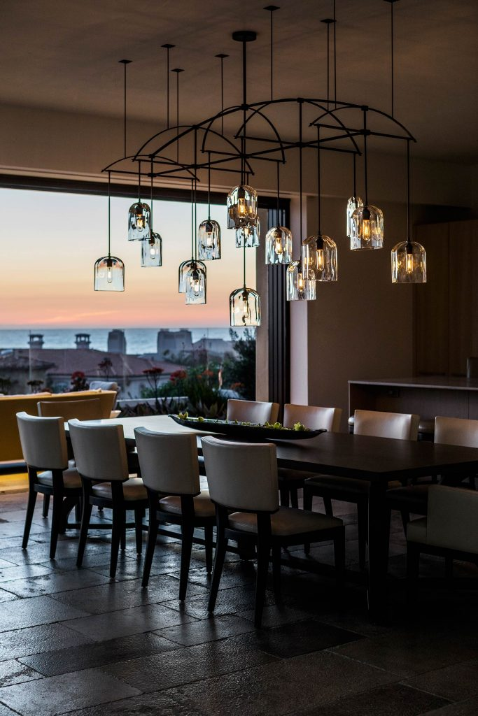 A chandelier over the dining table reflects the dramatic oceanview sunset