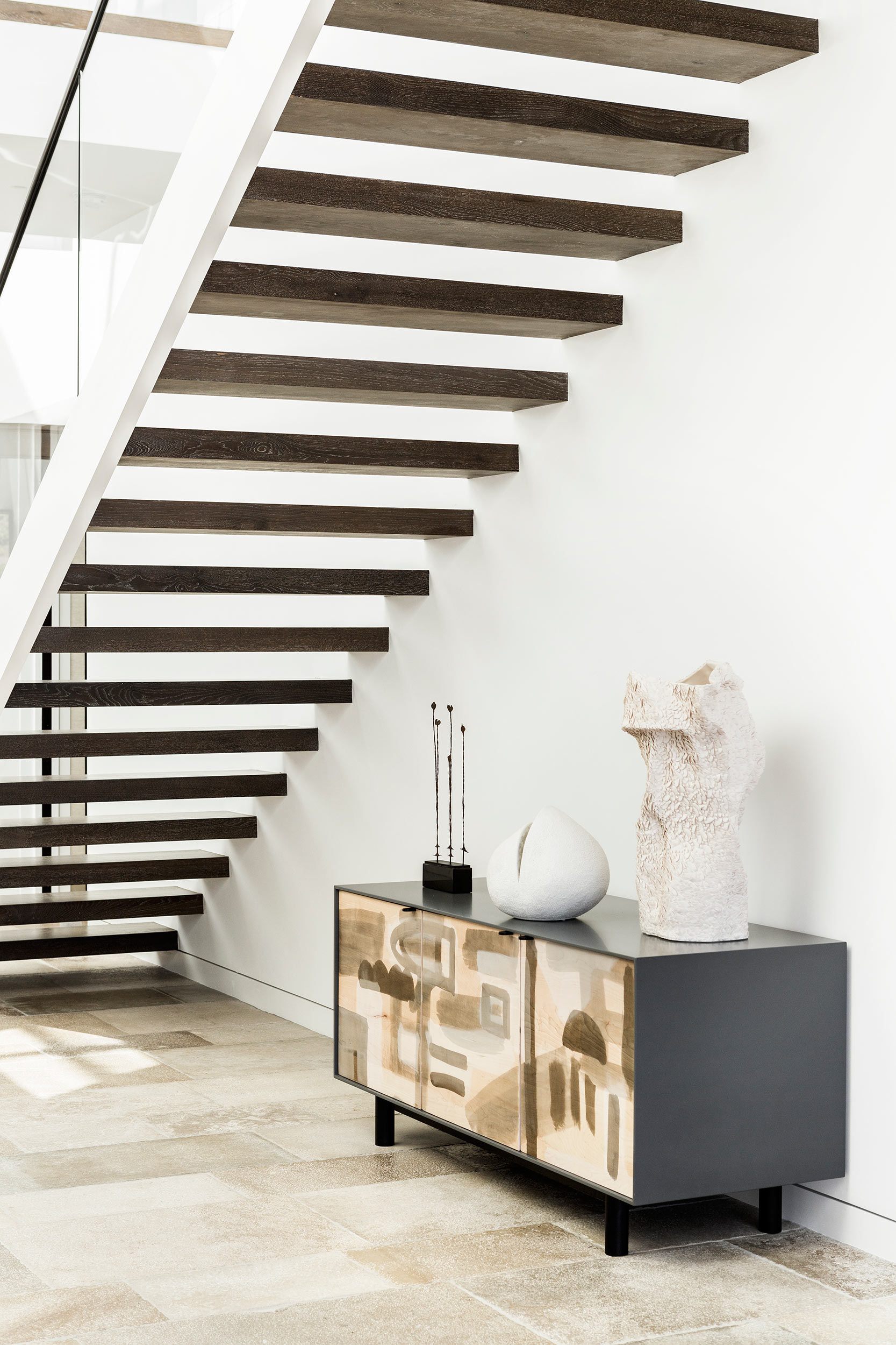 An open wood stair rises in the entry atrium