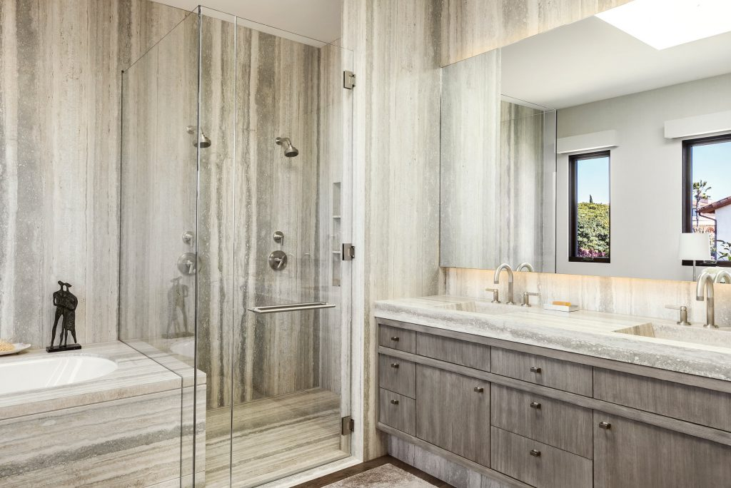 Stone and custom wood millwork shine in this custom master bathroom