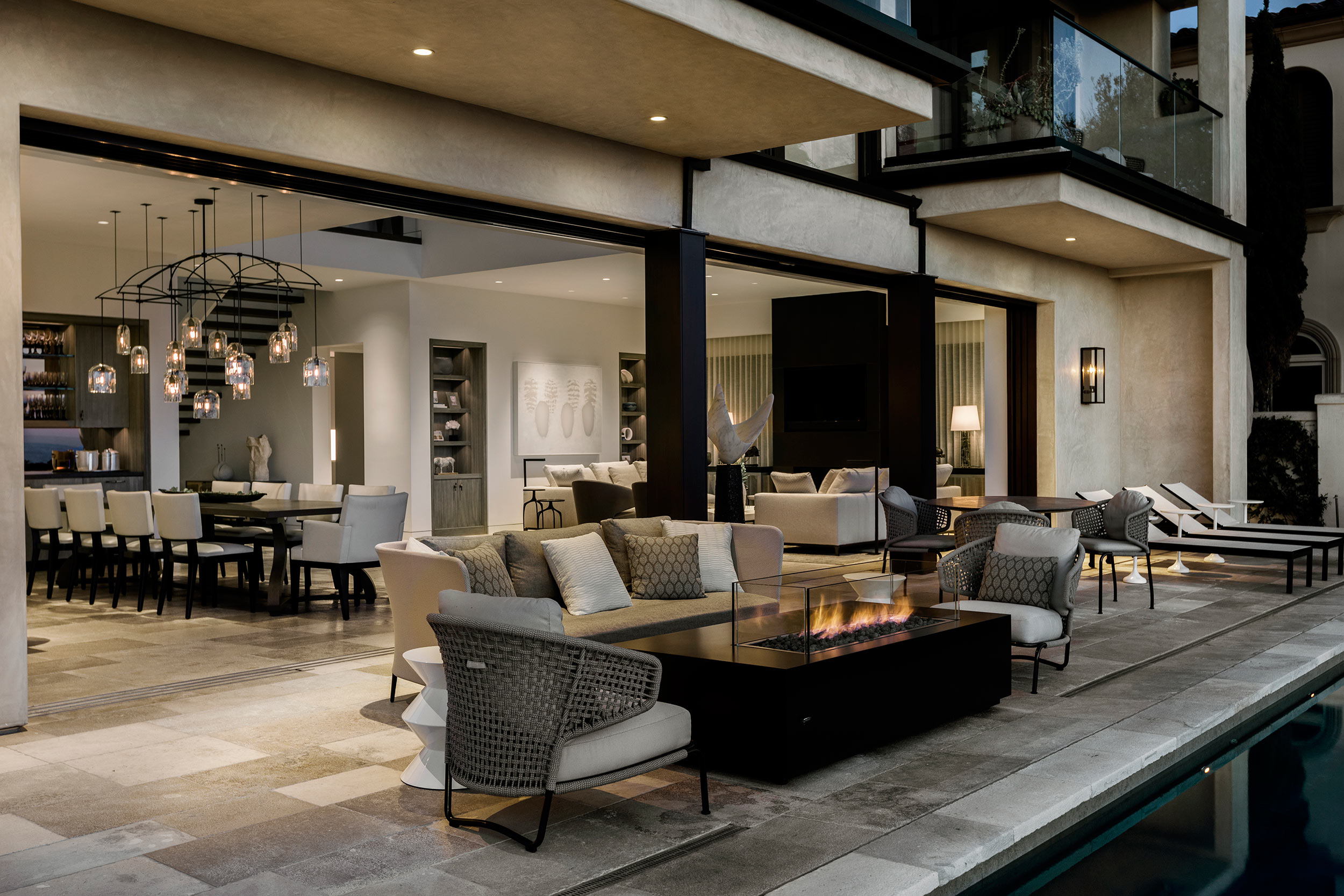 A seating area and custom fire table on the pool deck