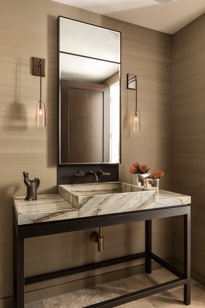 A custom metal and stone vanity makes a statement in the powder room