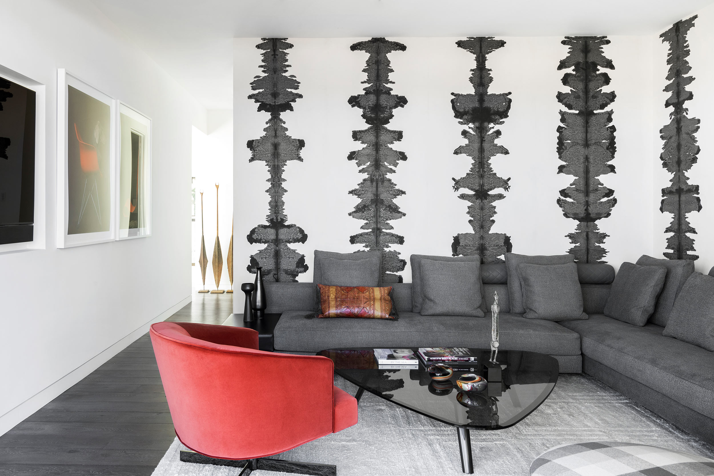 The den with Rorsach-inspired wallpaper in grey is accented with a red chair