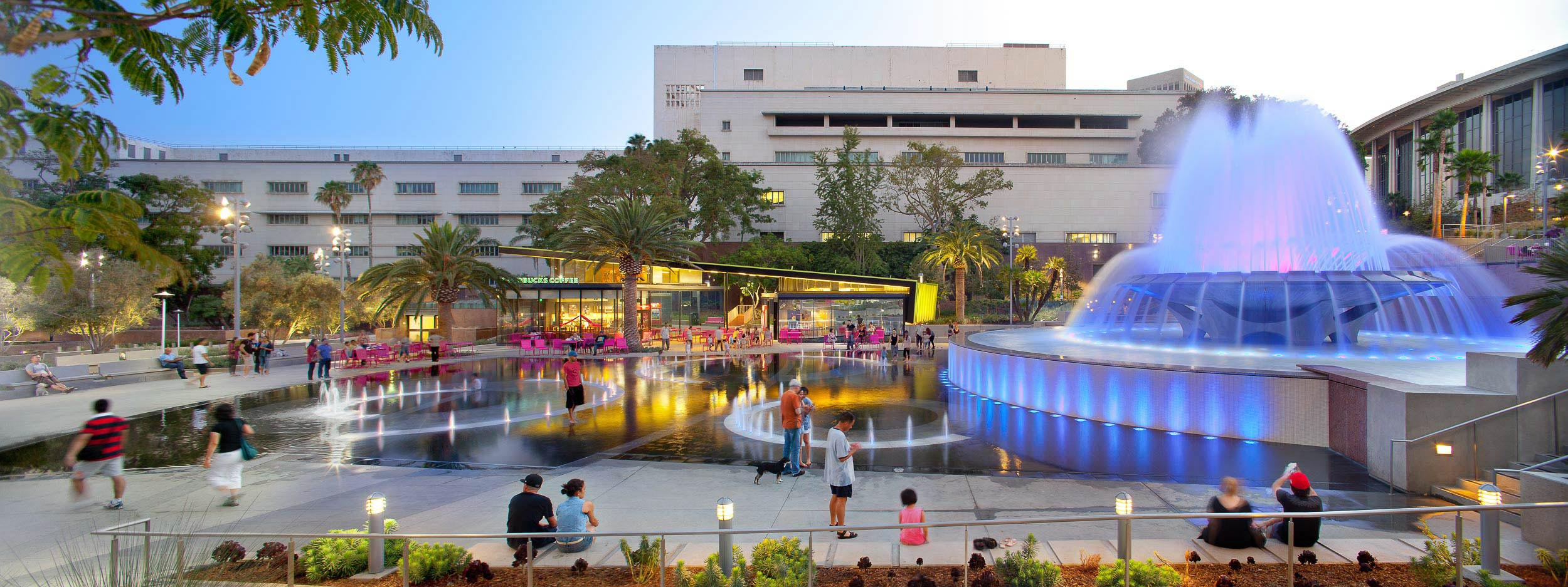 glowing park fountain with smaller water features on the ground beside it, and pink tables and seats in the background