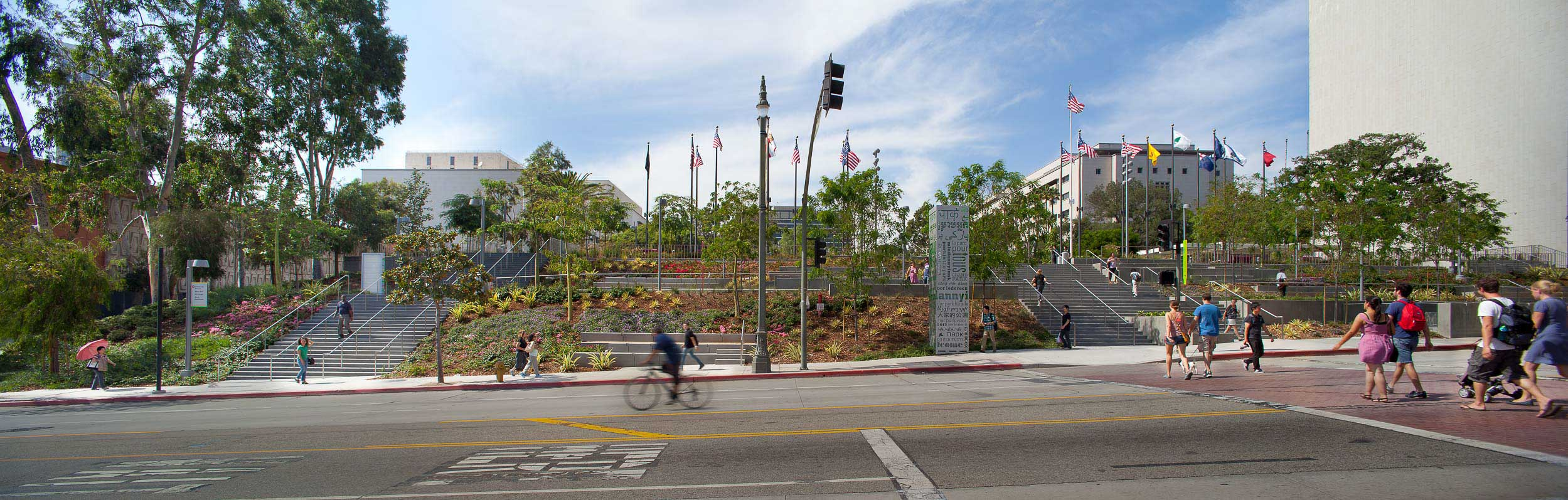 Street view of grand park stairs with people riding their bikes and pedestrians walking up