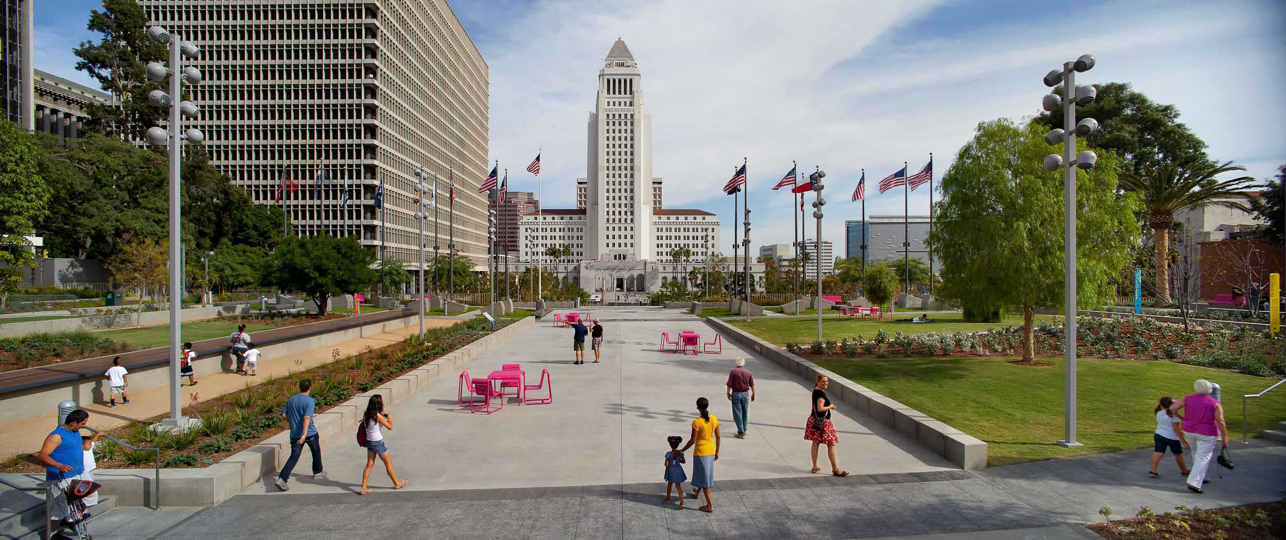 grand park pathway in between grassy lawns with people walking throughout the park and city hall in the center background
