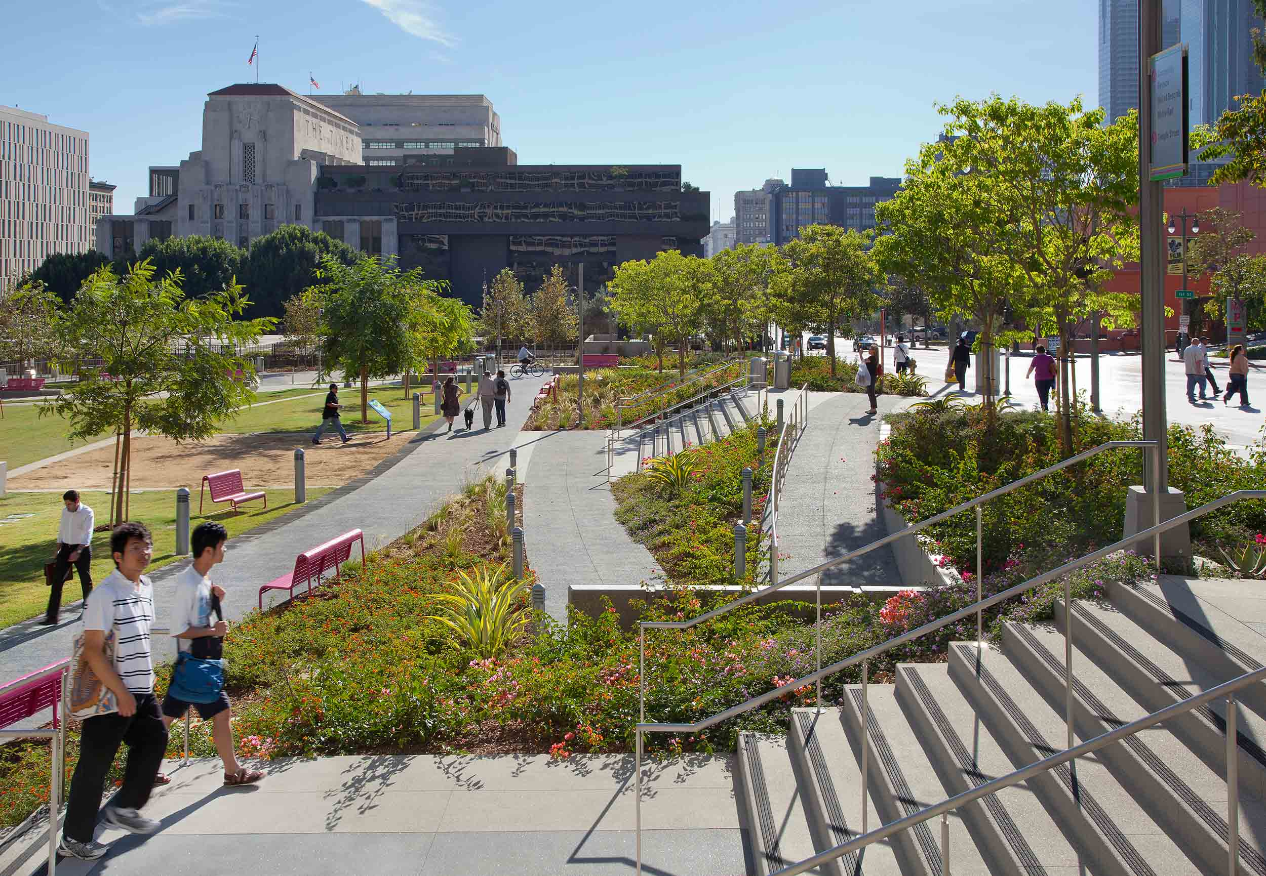 side view of people walking up stairs with intersecting curved paths in front of it, and plants along the sides of the stairs and paths