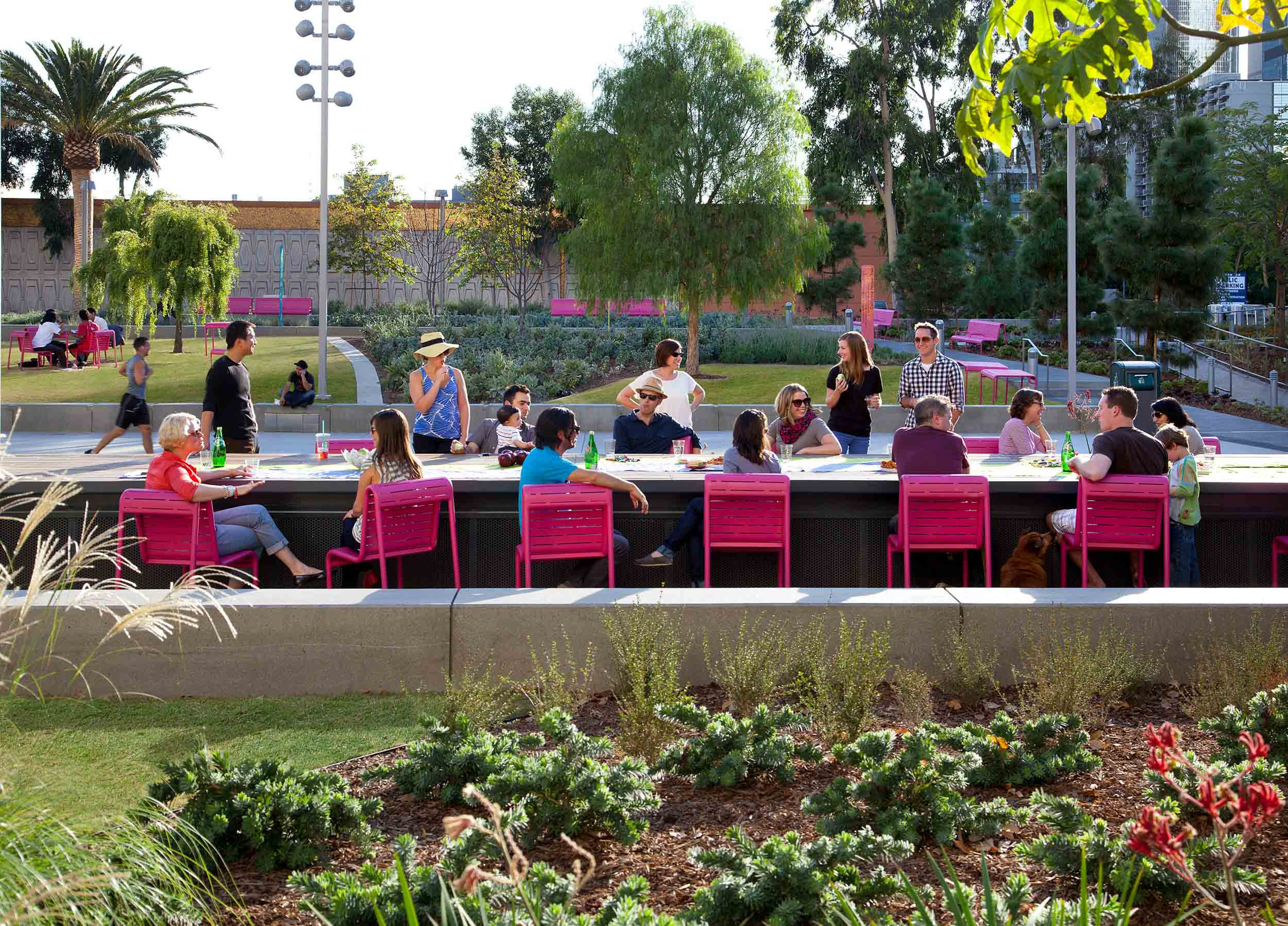people seated at pink chairs along a long outdoor dining table surrounded by trees and plants