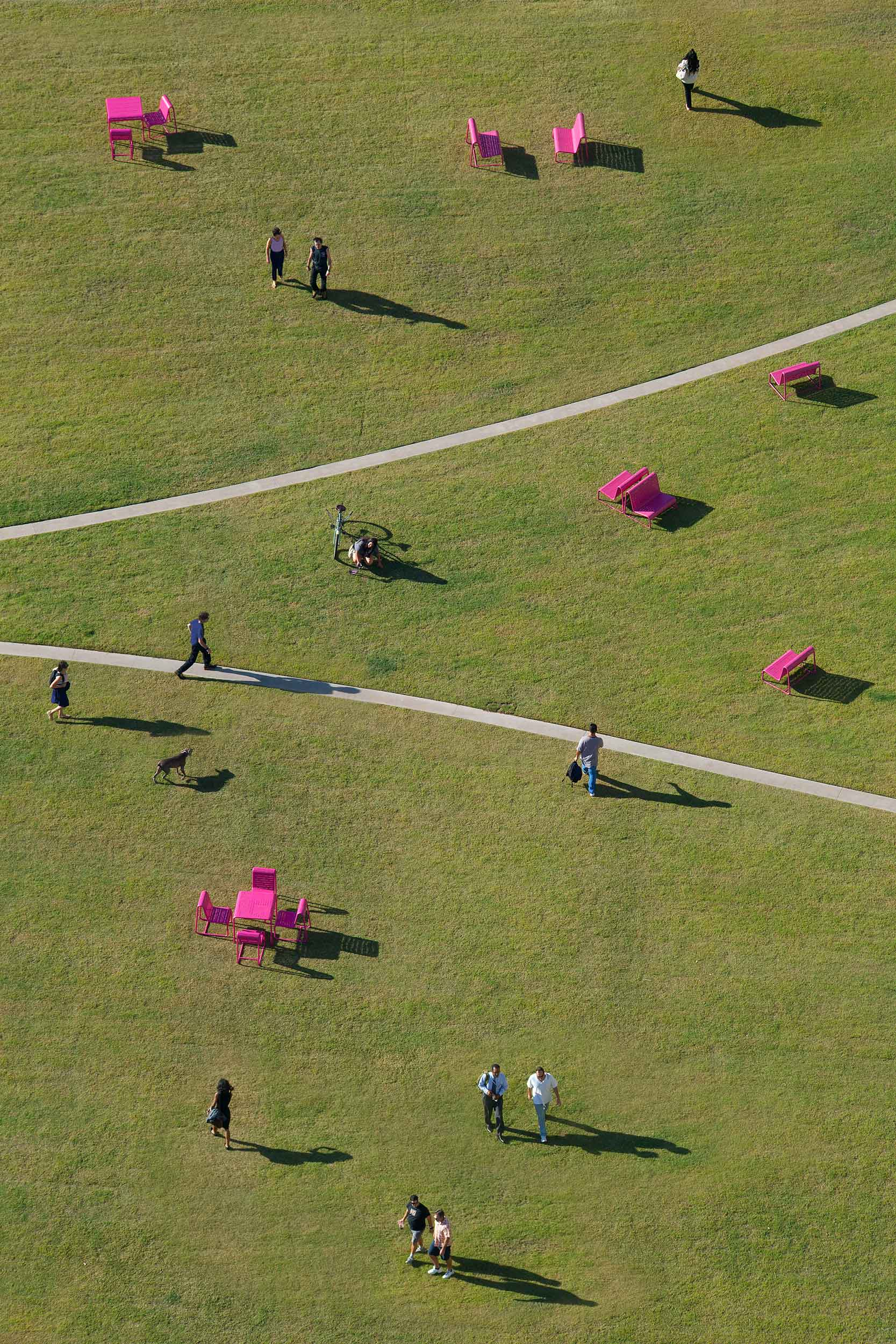aerial view of grassy lawn with people and pink seating scattered throughout, with two curved paths running through the center