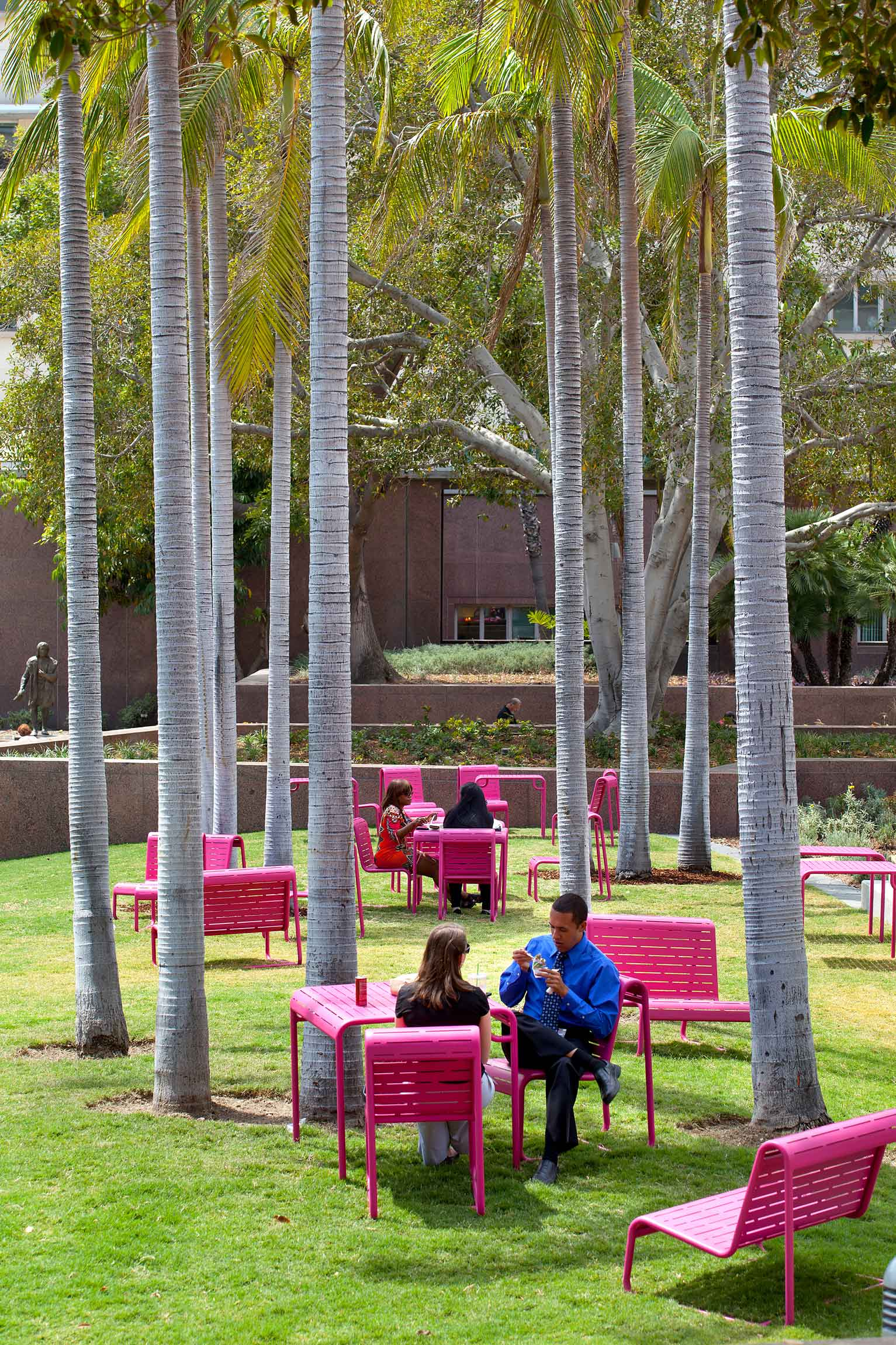 people eating at a pink table set on a grassy lawn under a tree