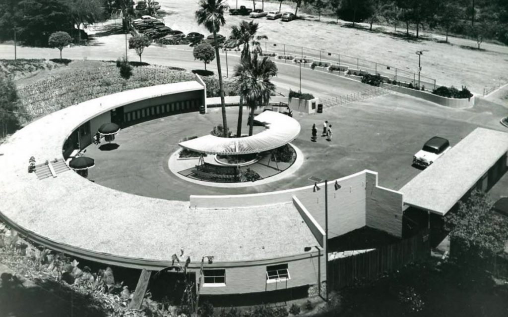 A black and white photo with a semicircular buildign and structure at the early H