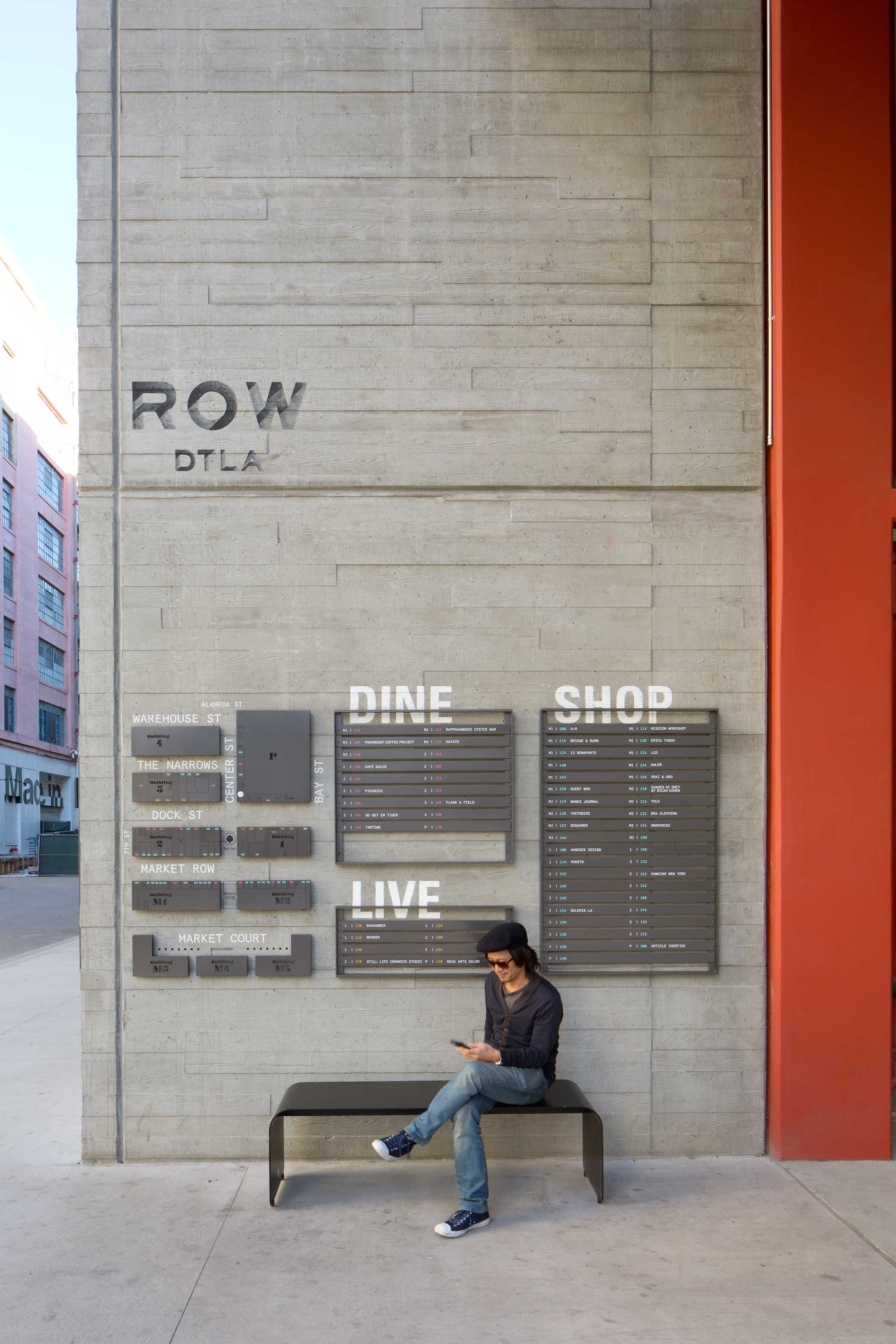 woman sitting on a bench against a cement wall with a ROW map above her head