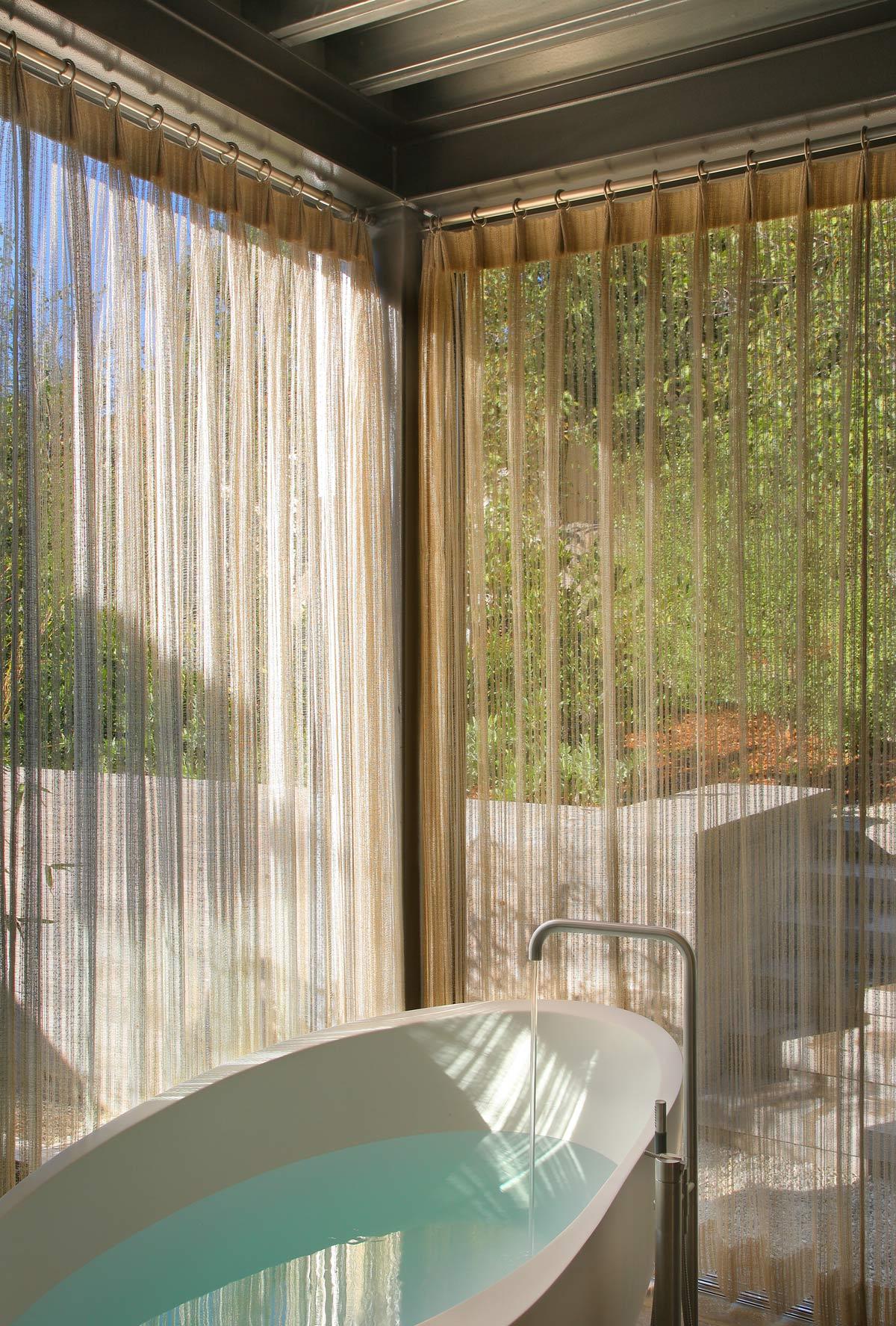 soaking tub behind sheer curtains