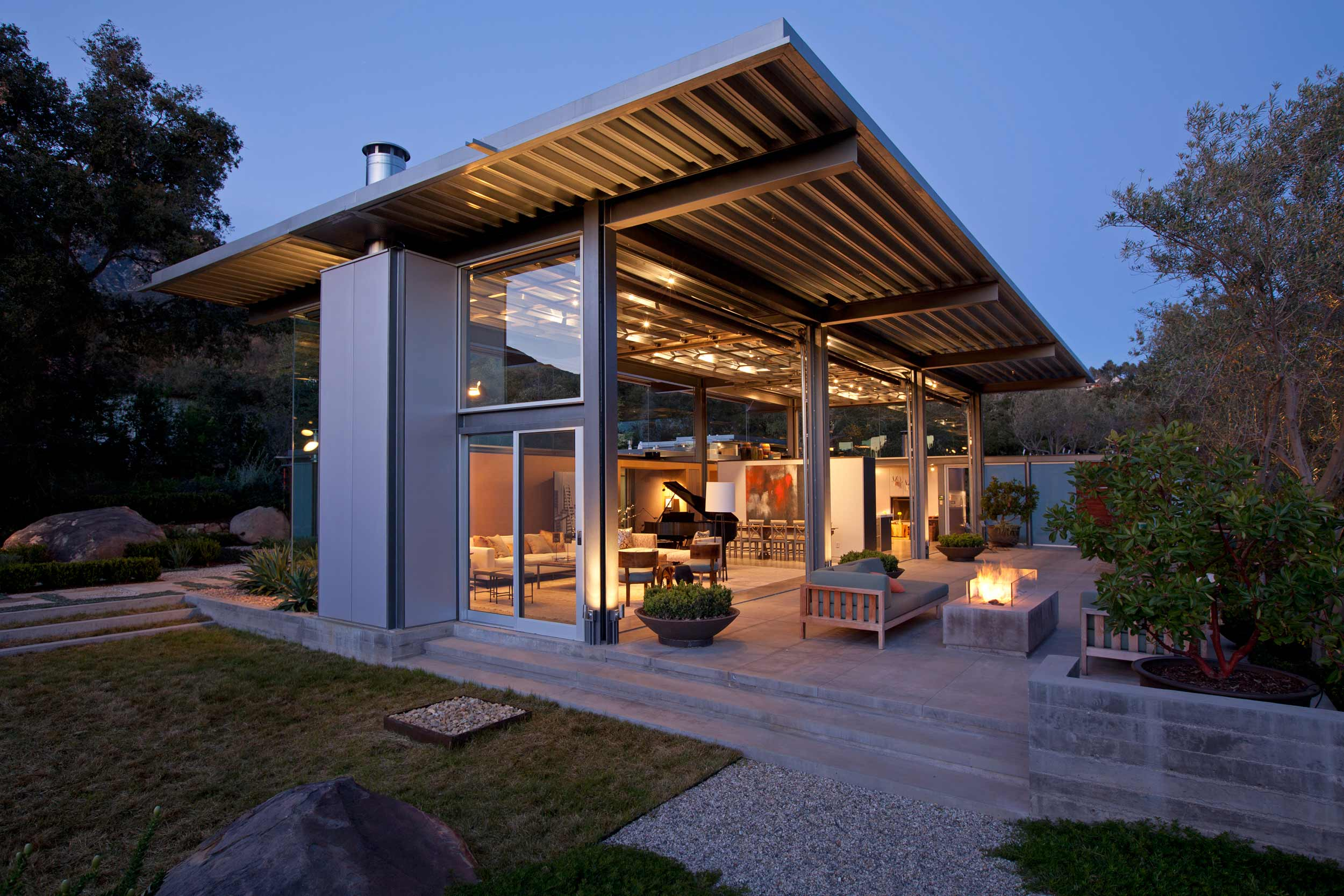 home and garden at dusk with architectural overhang roof