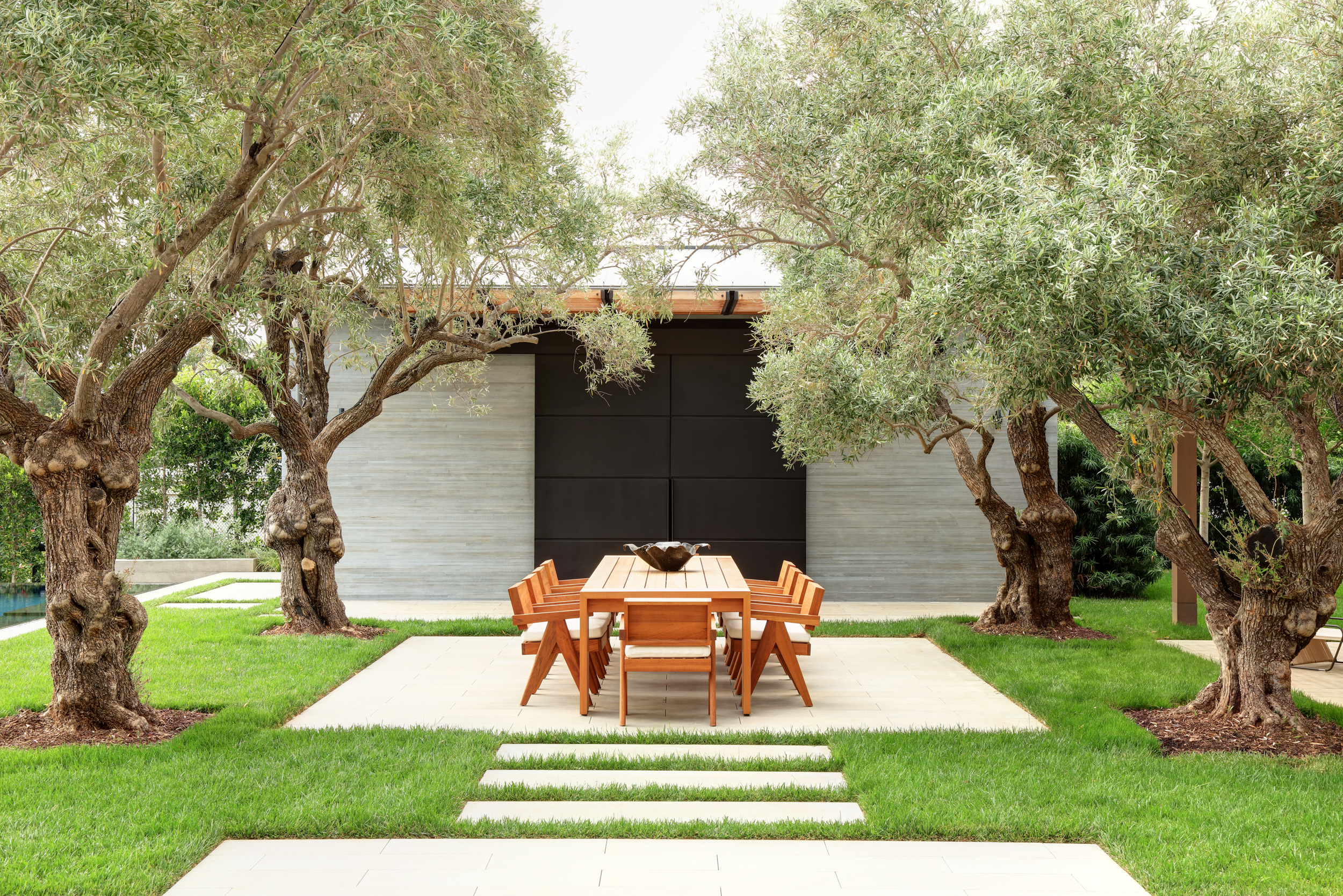 grass courtyard with central square cement floor and mature trees in each corner