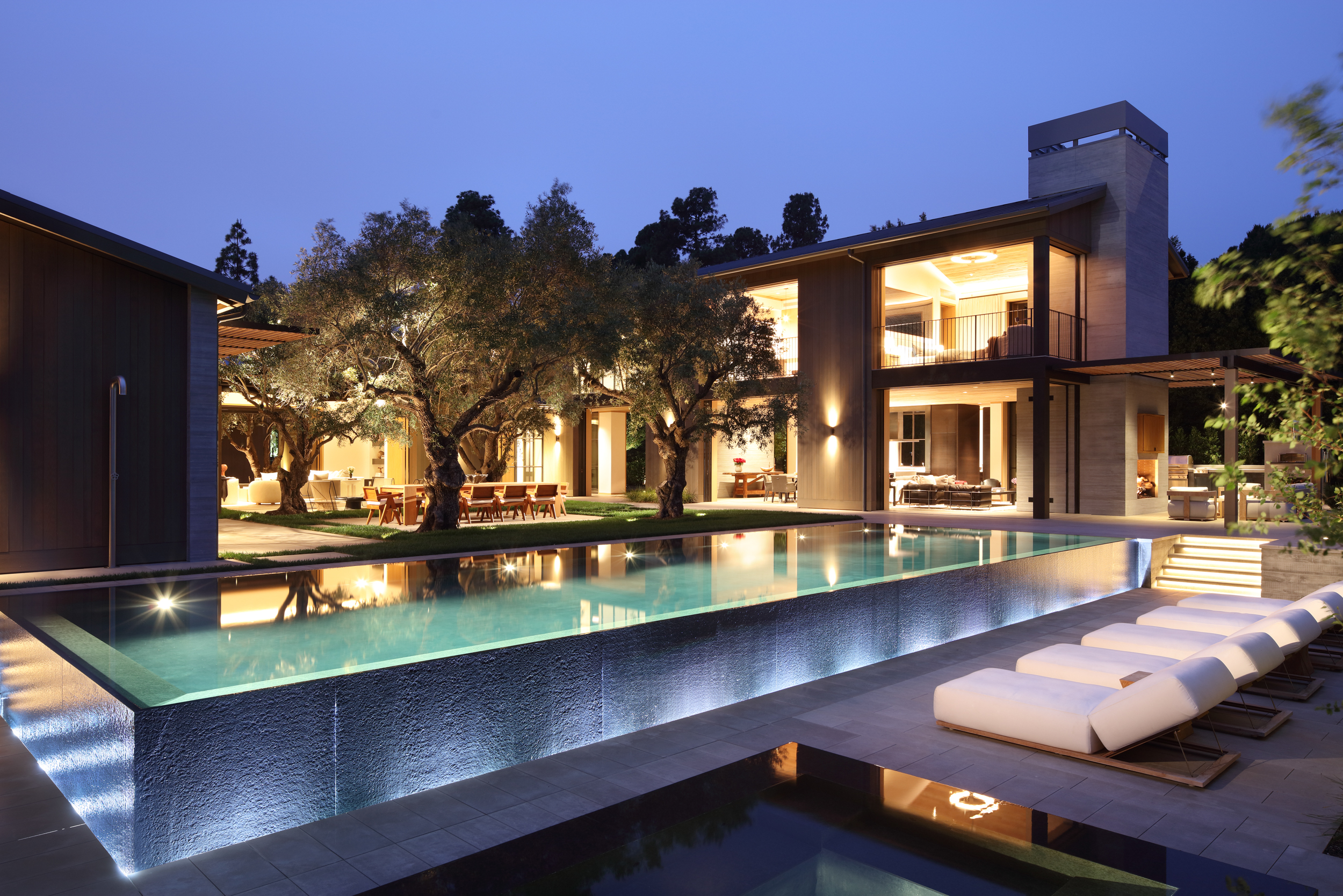 infinity pool and surrounding courtyard at dusk with lounge chairs