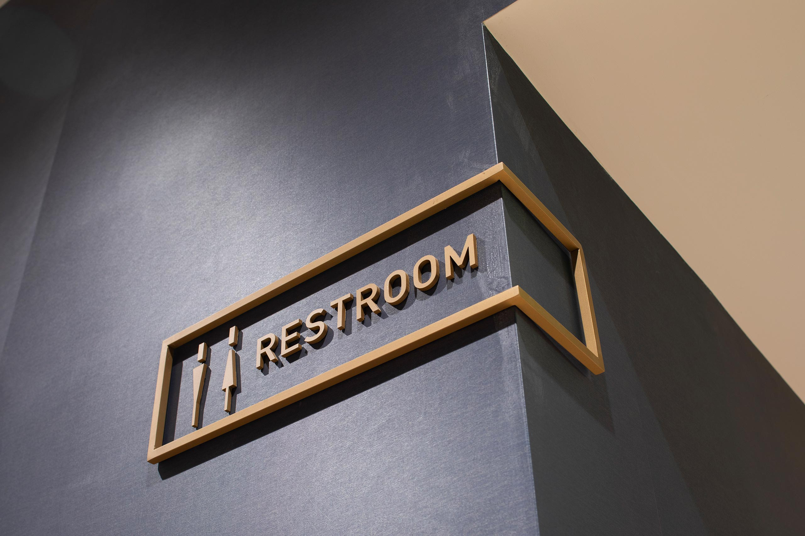 metal restroom sign wrapped around corner on dark grey wall