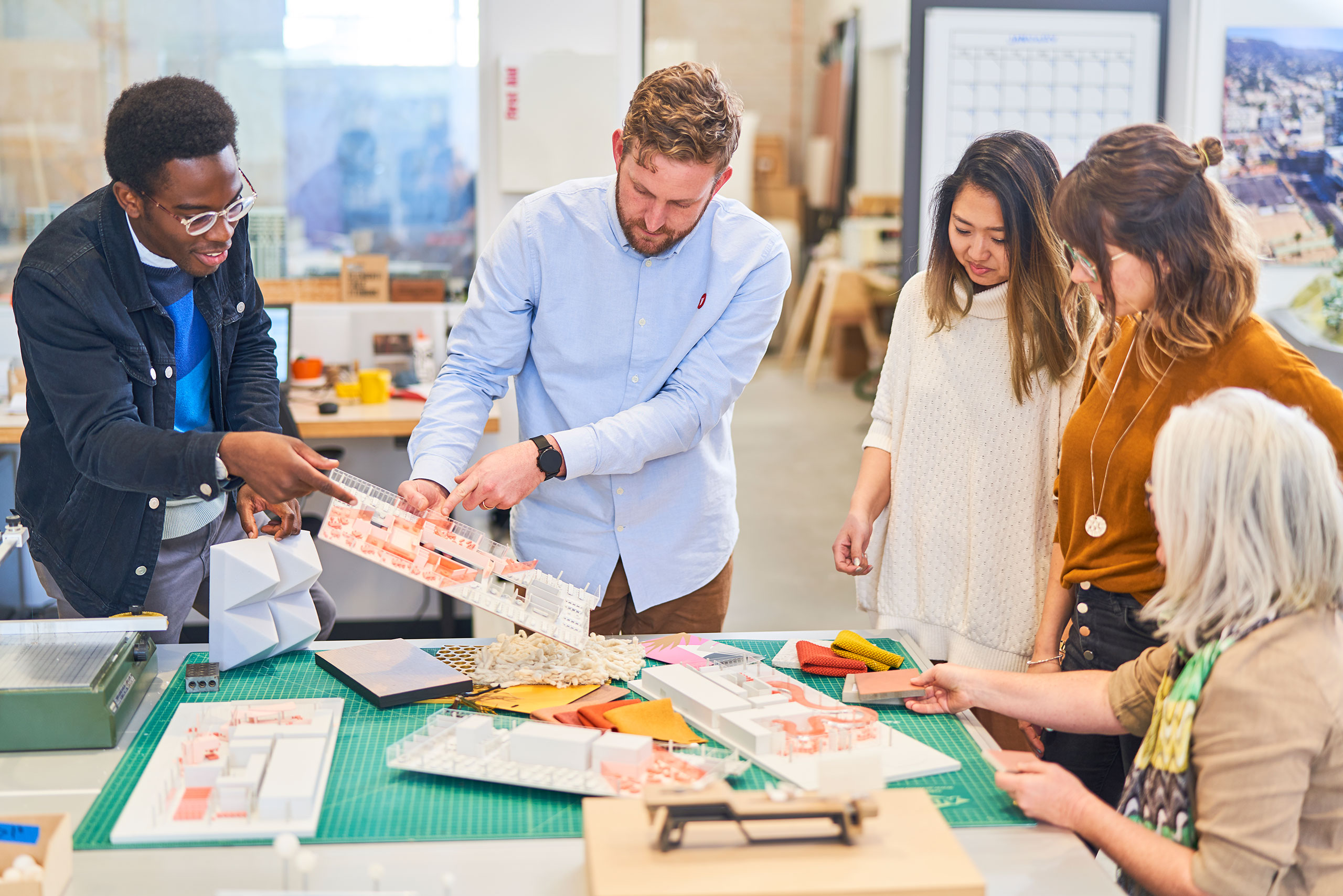 People working around a table with building models and materials