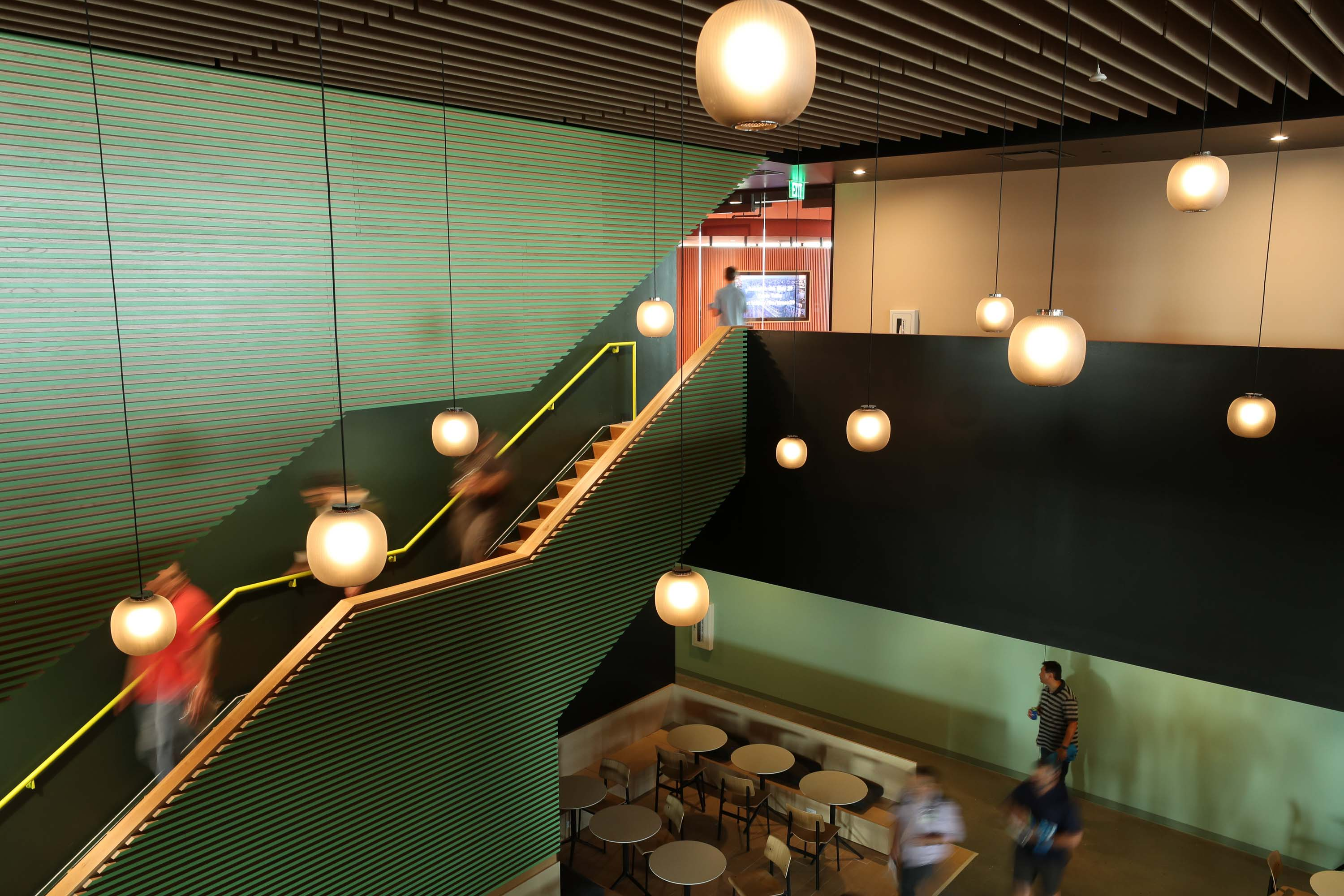 green stairs with people walking down and orb pendant lights hanging from the ceiling