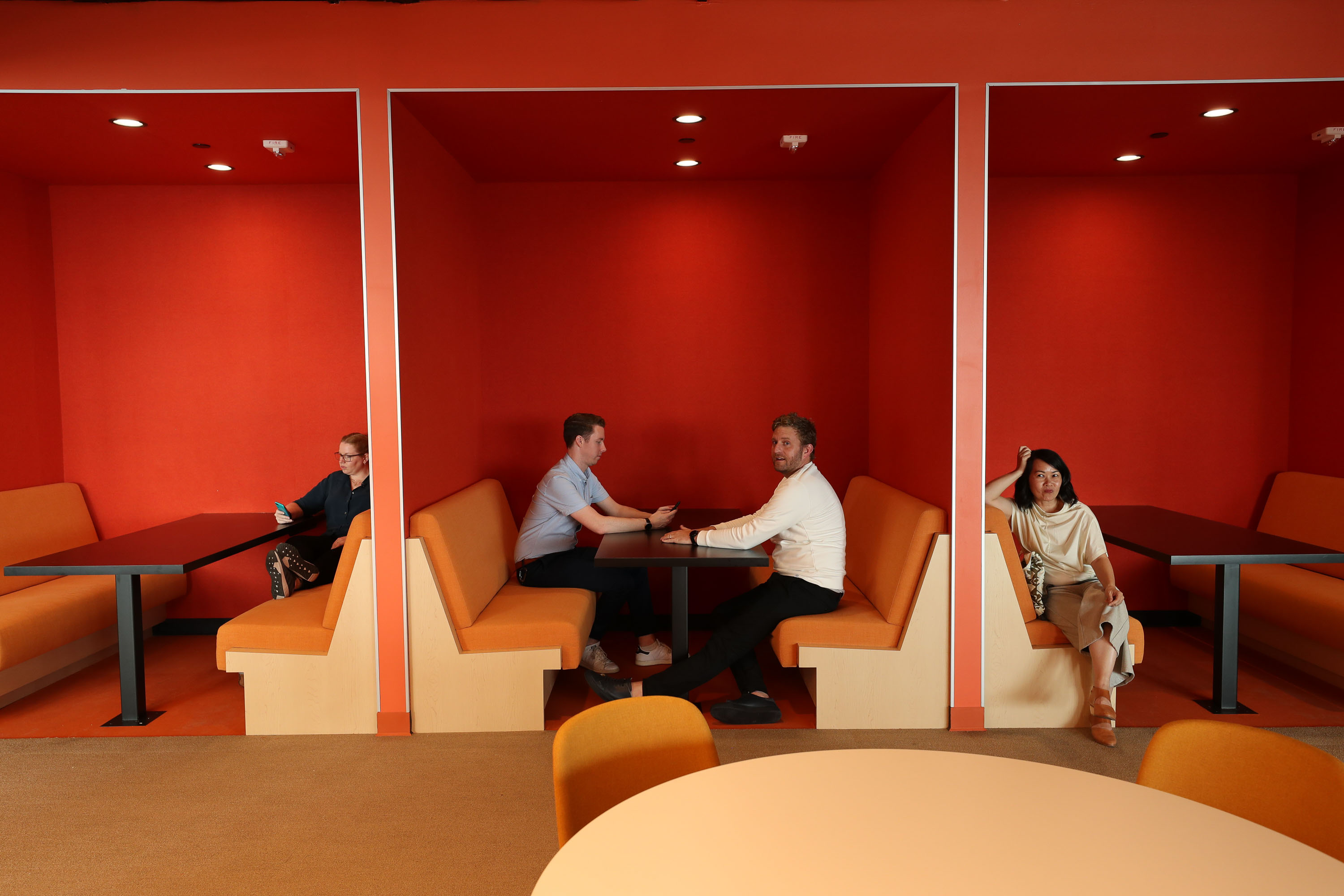people sitting in orange booth seating with red walls