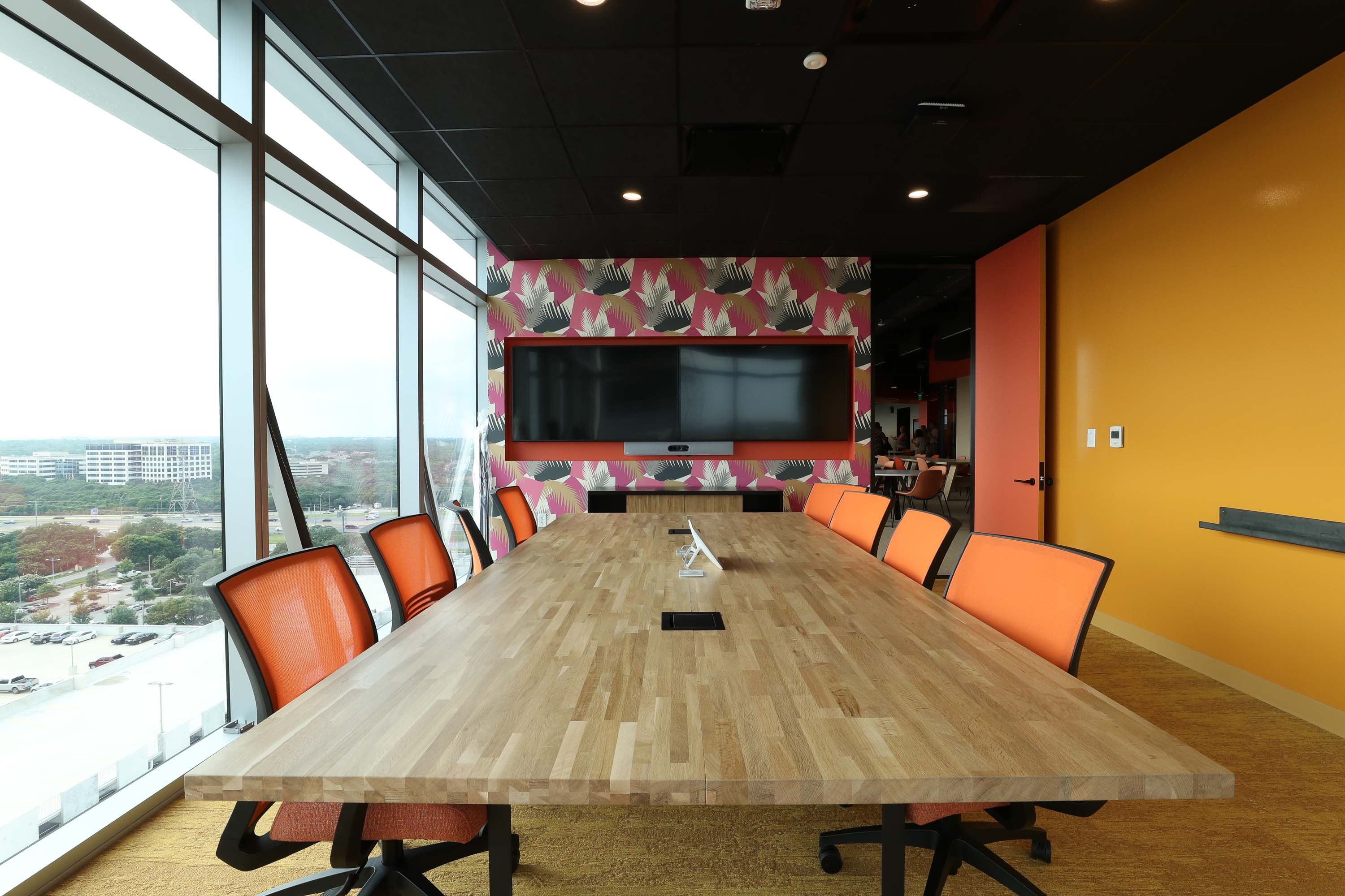 meeting room interior with big collaboration table, wall to wall windows to the left, an orange wall to the right, and a printed wallpaper in the back