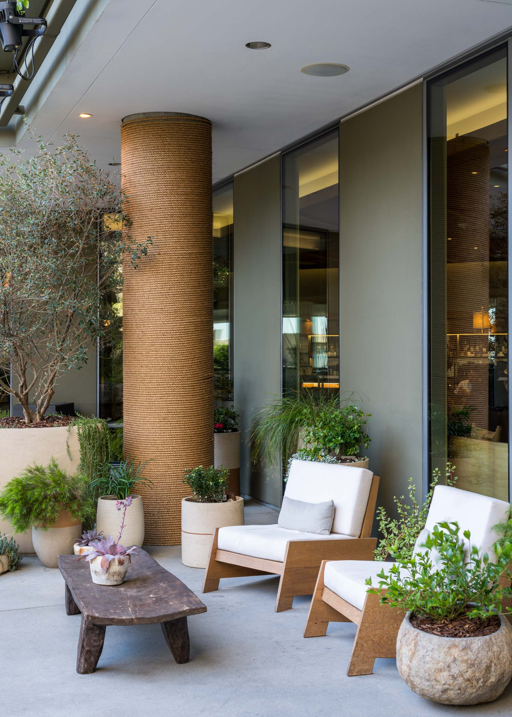 outdoor lounge with modern white chairs and jute wrapped pole