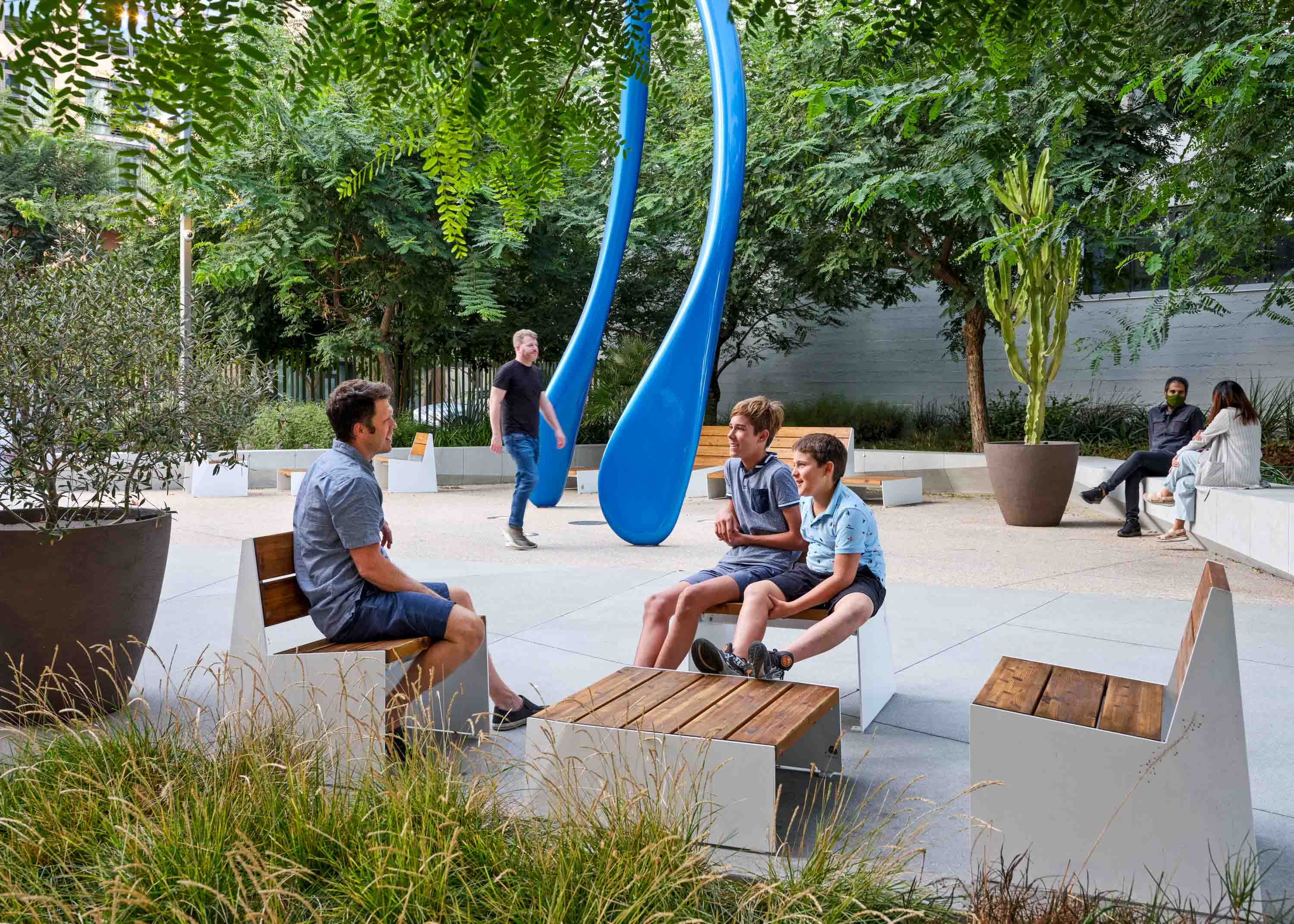 man seated with two kids on wooden furniture with a large blue sculpture in the background