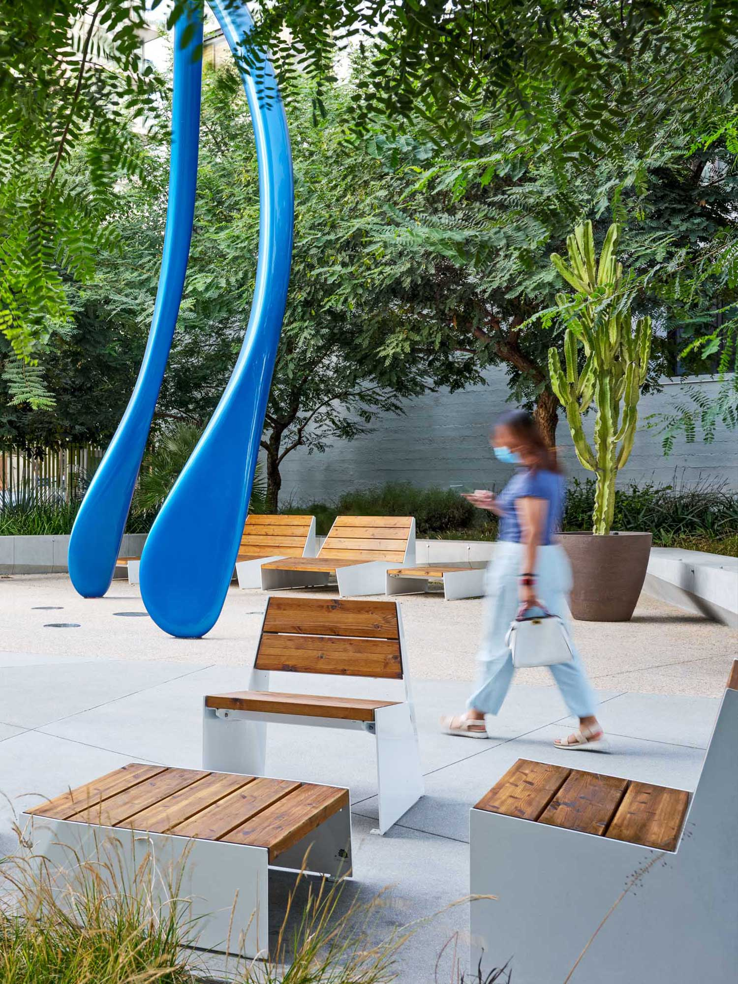 woman walking through a courtyard filled with wooden furniture and a large blue sculpture