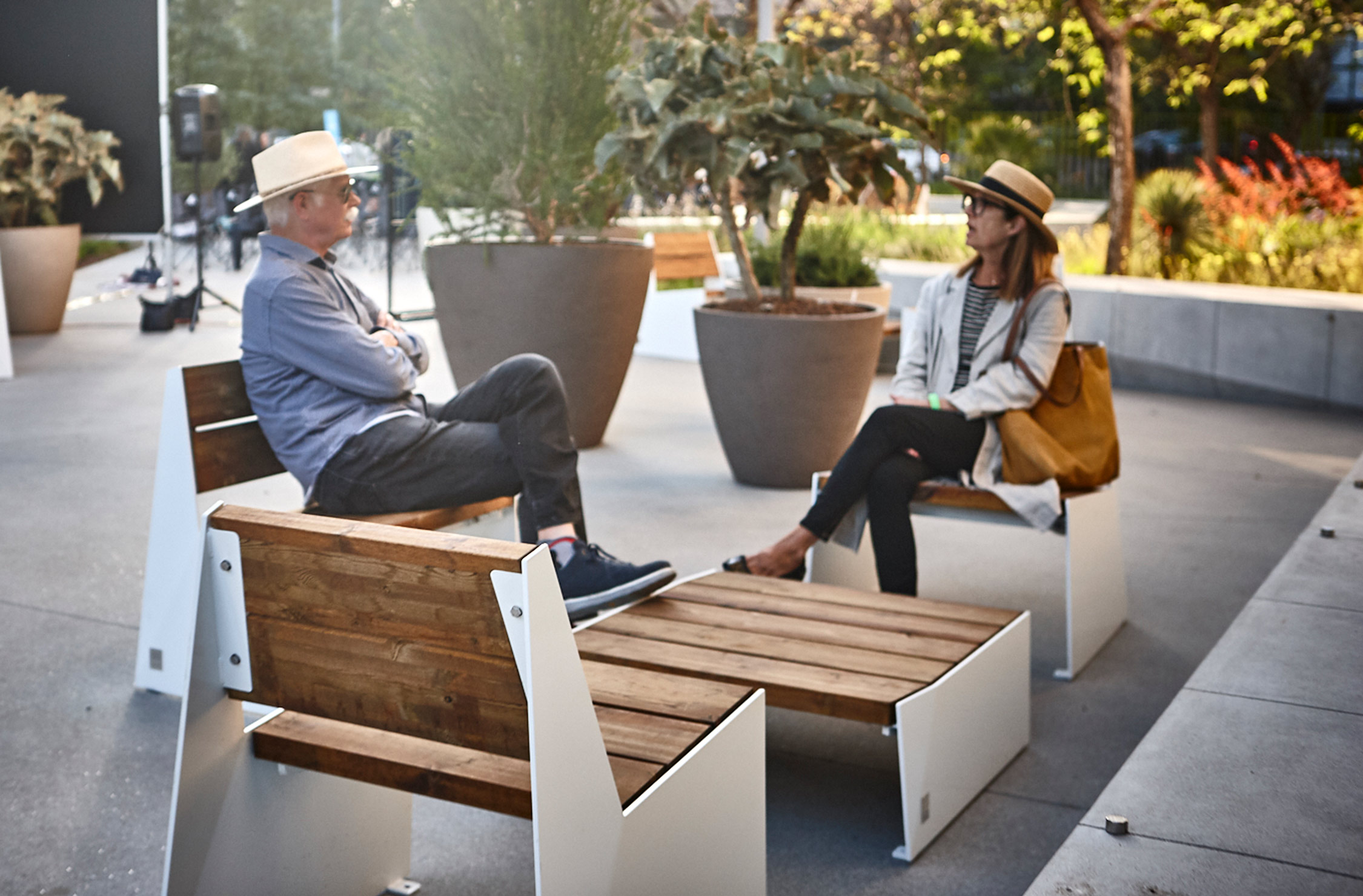 people seated on wooden furniture with planters behind them