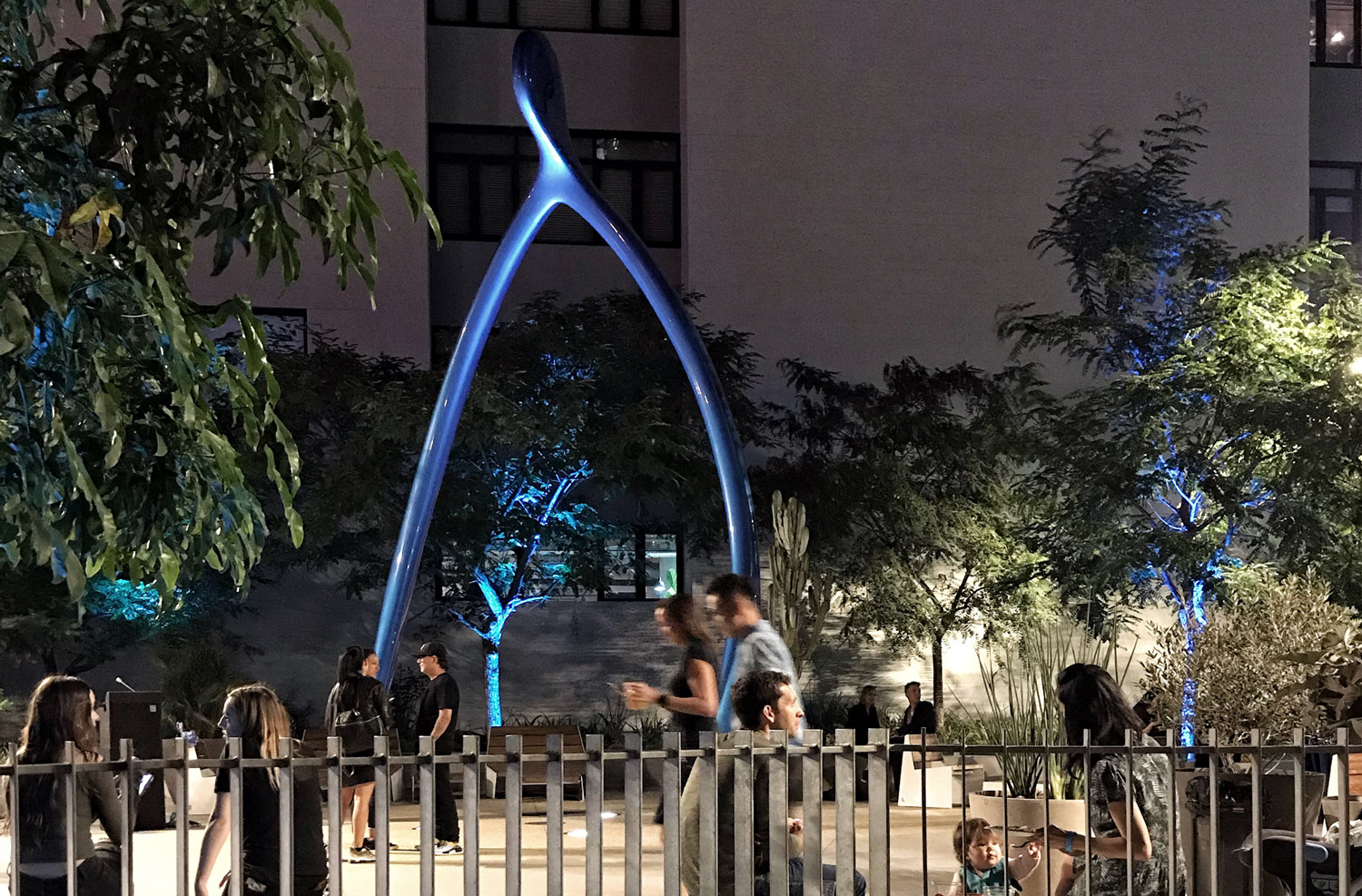 night shot of people in a courtyard with a large blue sculpture in the background