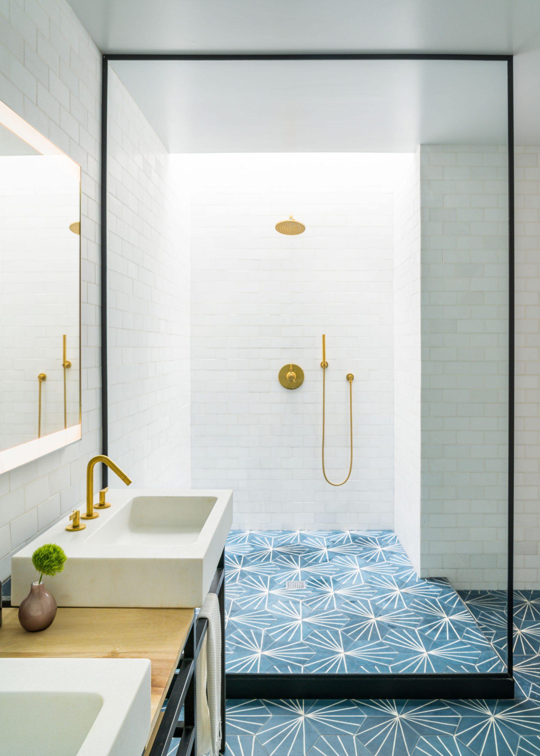 brightly lit shower with white tile and gold fixtures