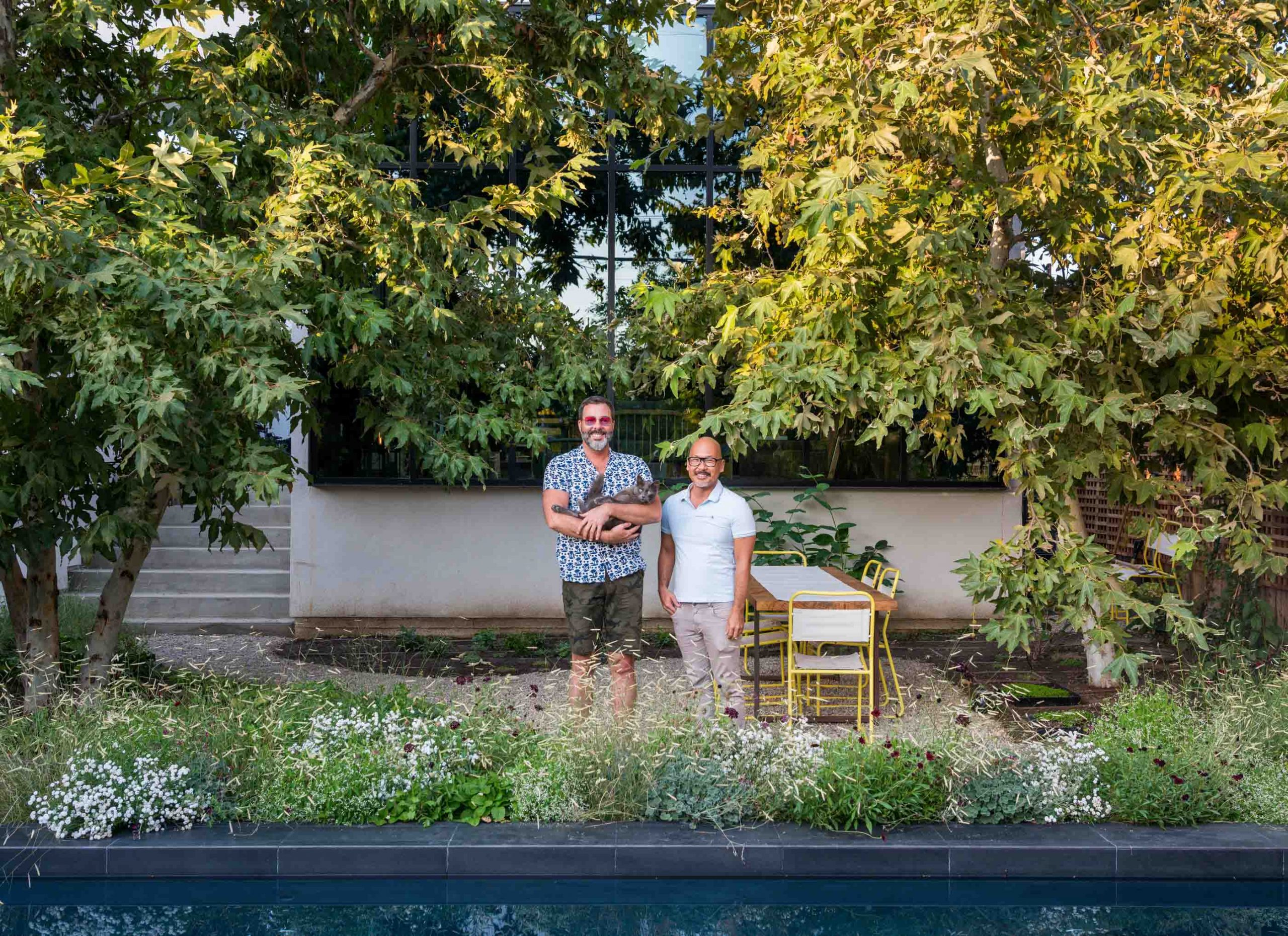 two men smiling and holding cat in verdant backyard by pool