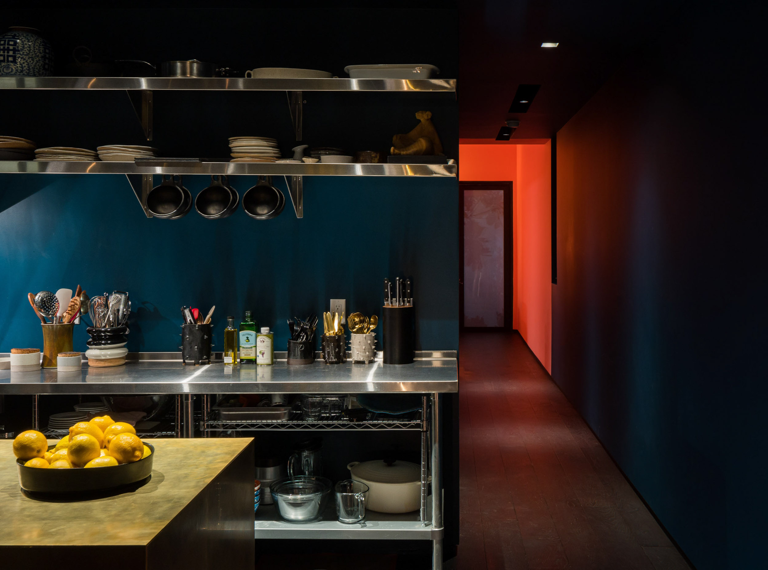 modern kitchen with blue wall and red hallway