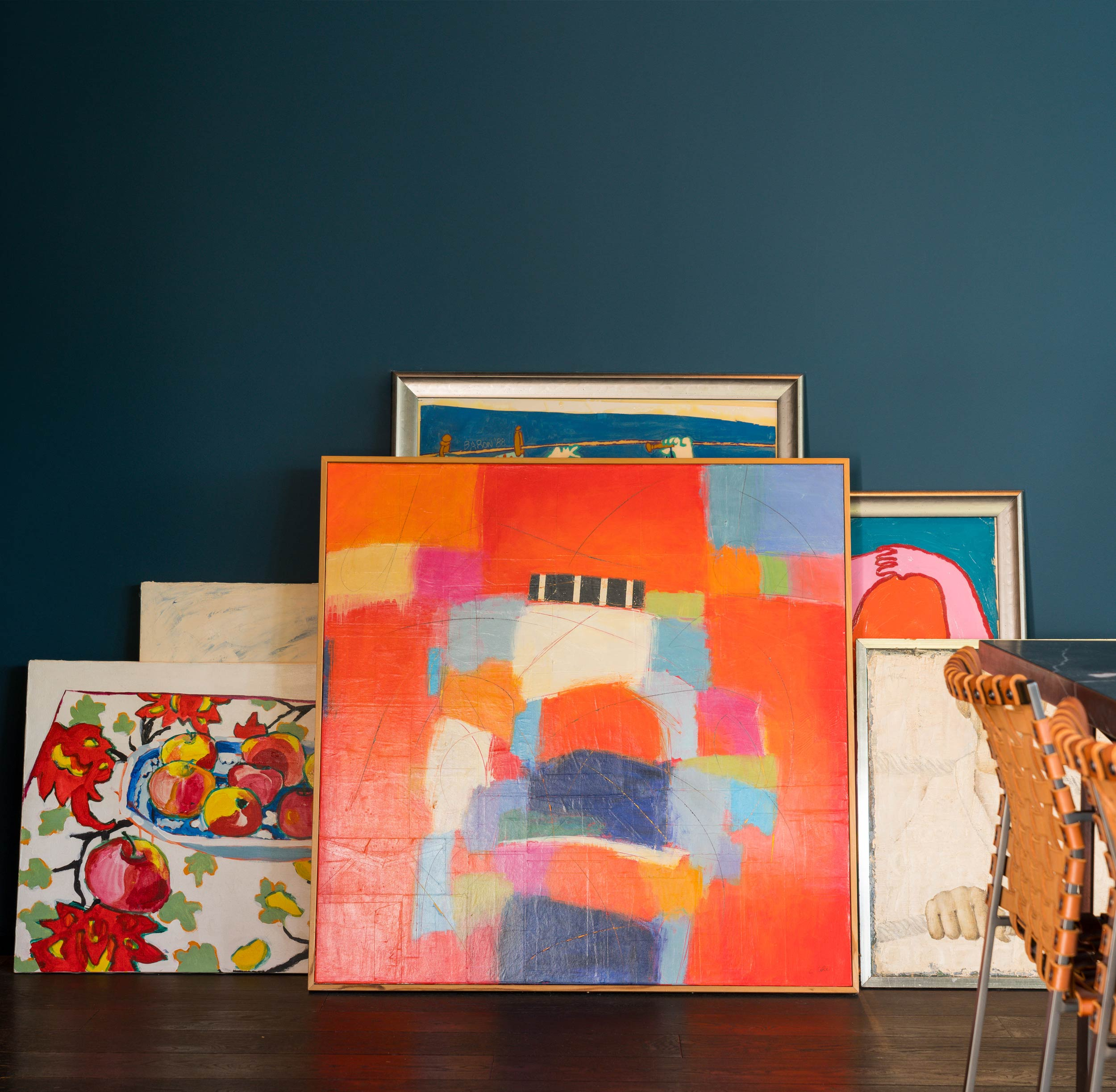 brightly colored abstract paintings leaning against wall
