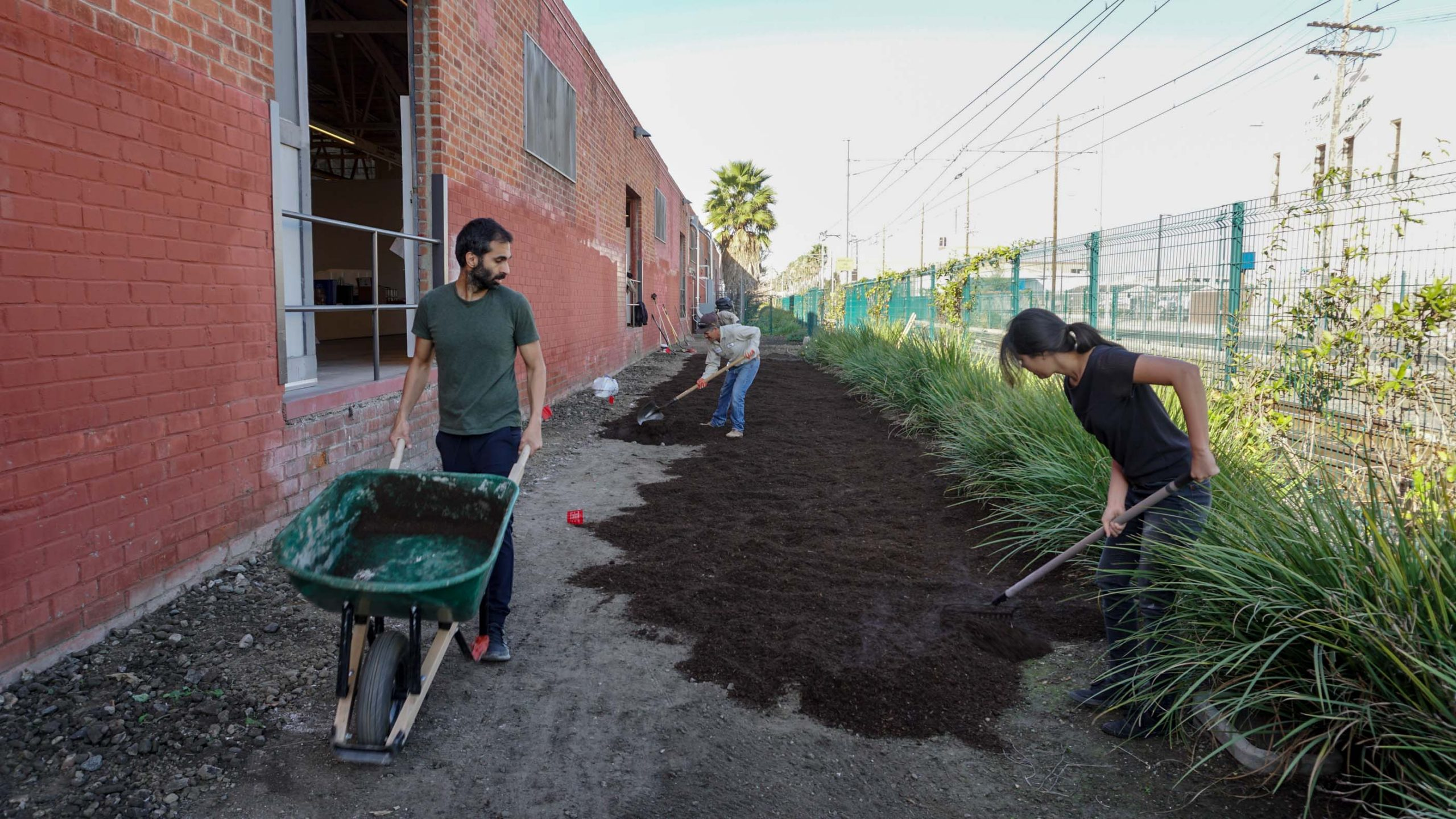 man with wheel barrow and woman raking soil