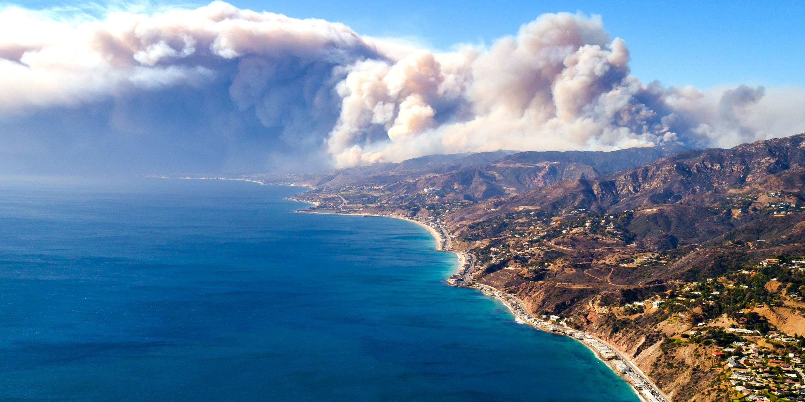 beachside mountains with the Woolsey fire burning in the back mountains
