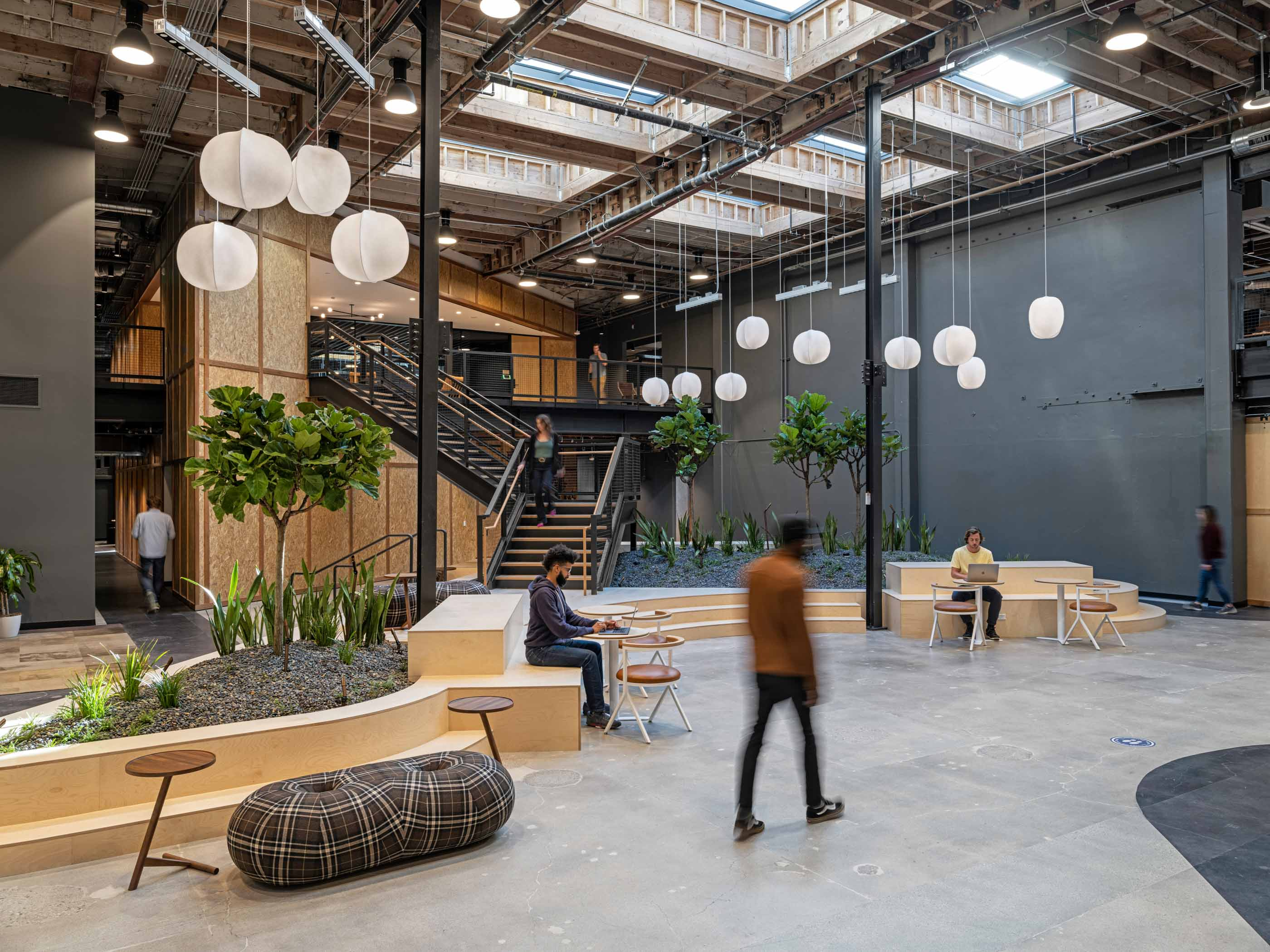 people working at desks in a common area with stairs and plants behind them and paper lanterns hanging from the ceiling