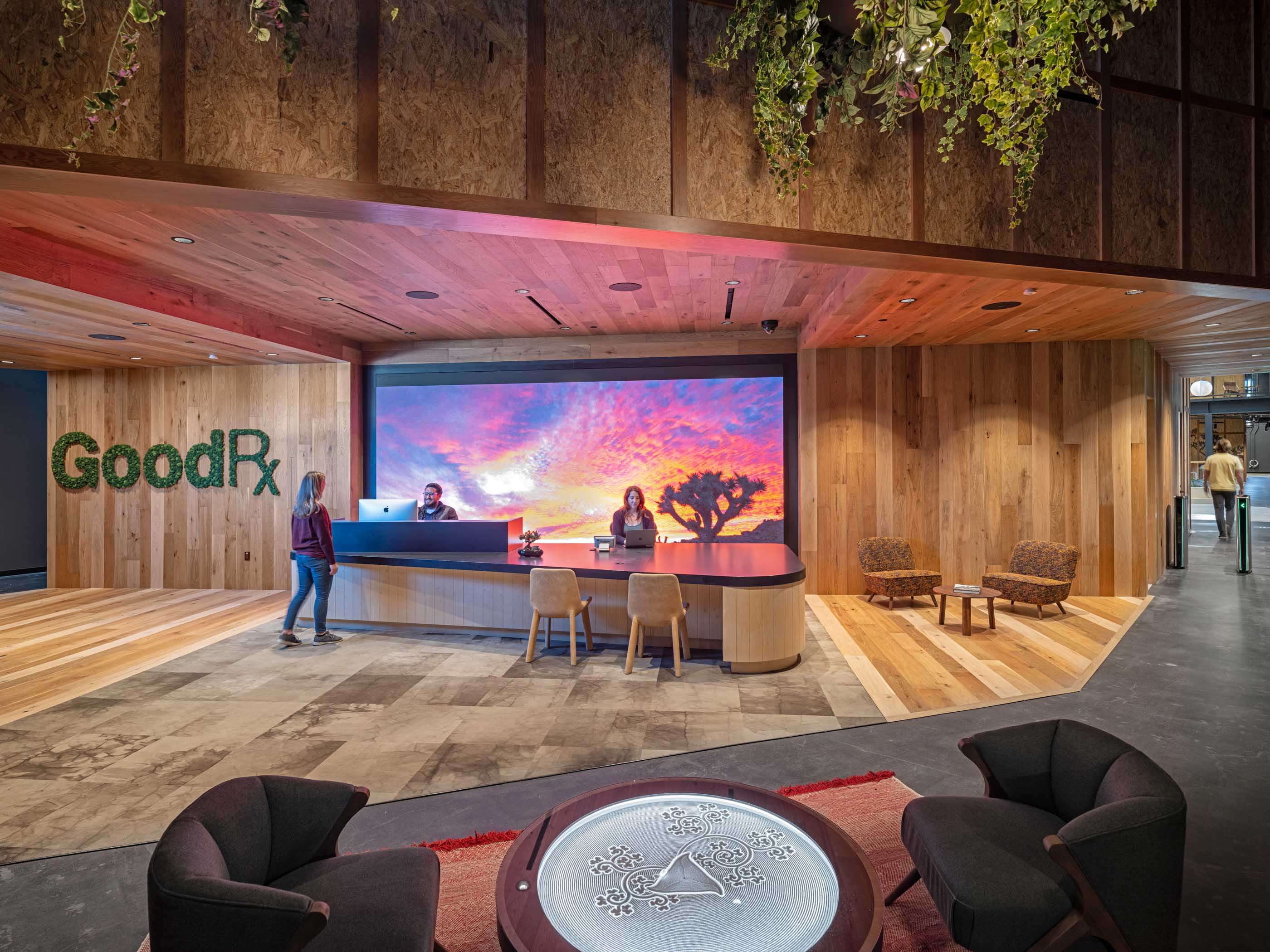 GoodRx lobby front desk with screen showing a sunset on the wall and plants hanging from the ceiling