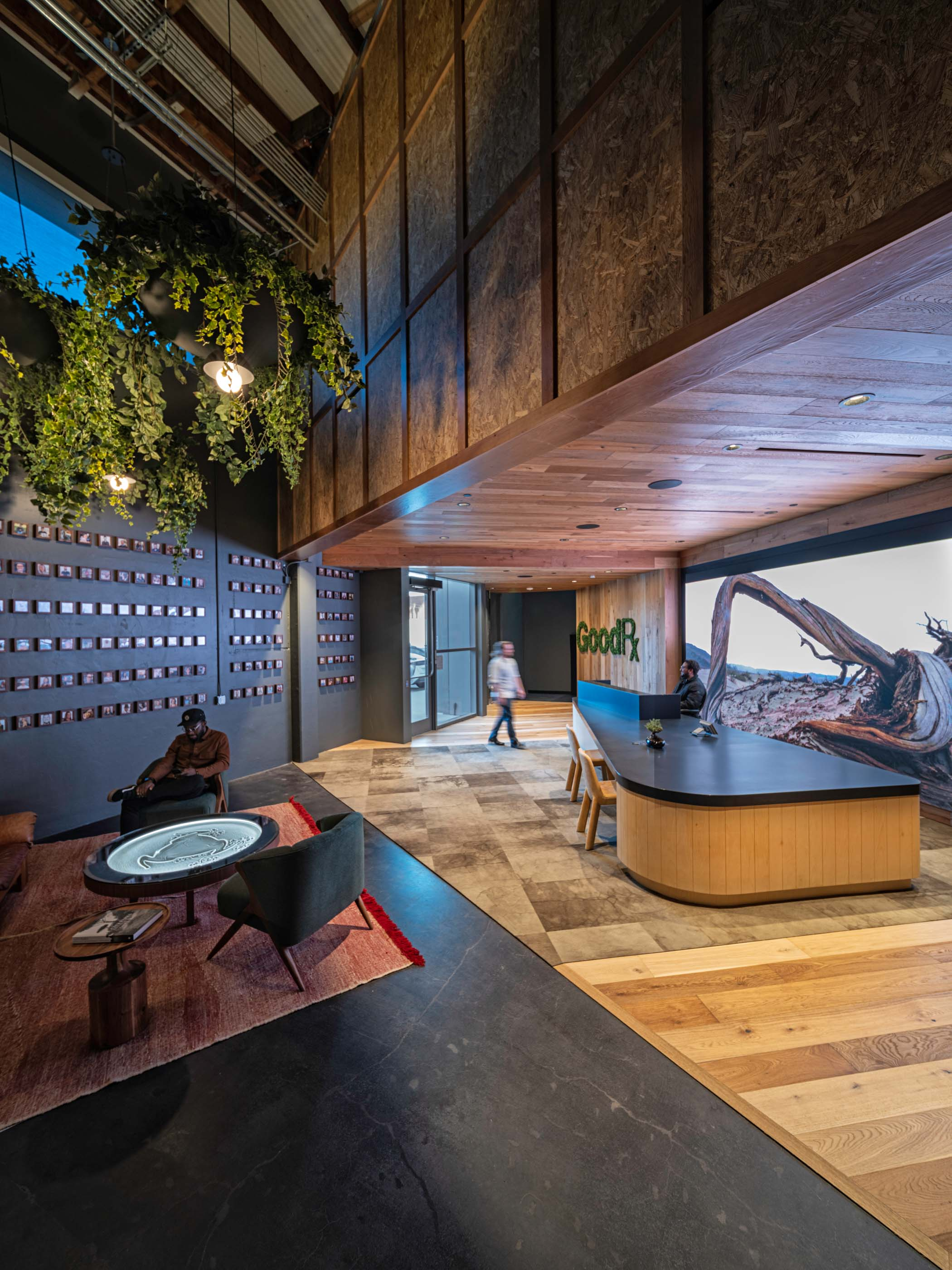 Good Rx lobby entrance with a front desk, a table, and wood finishes