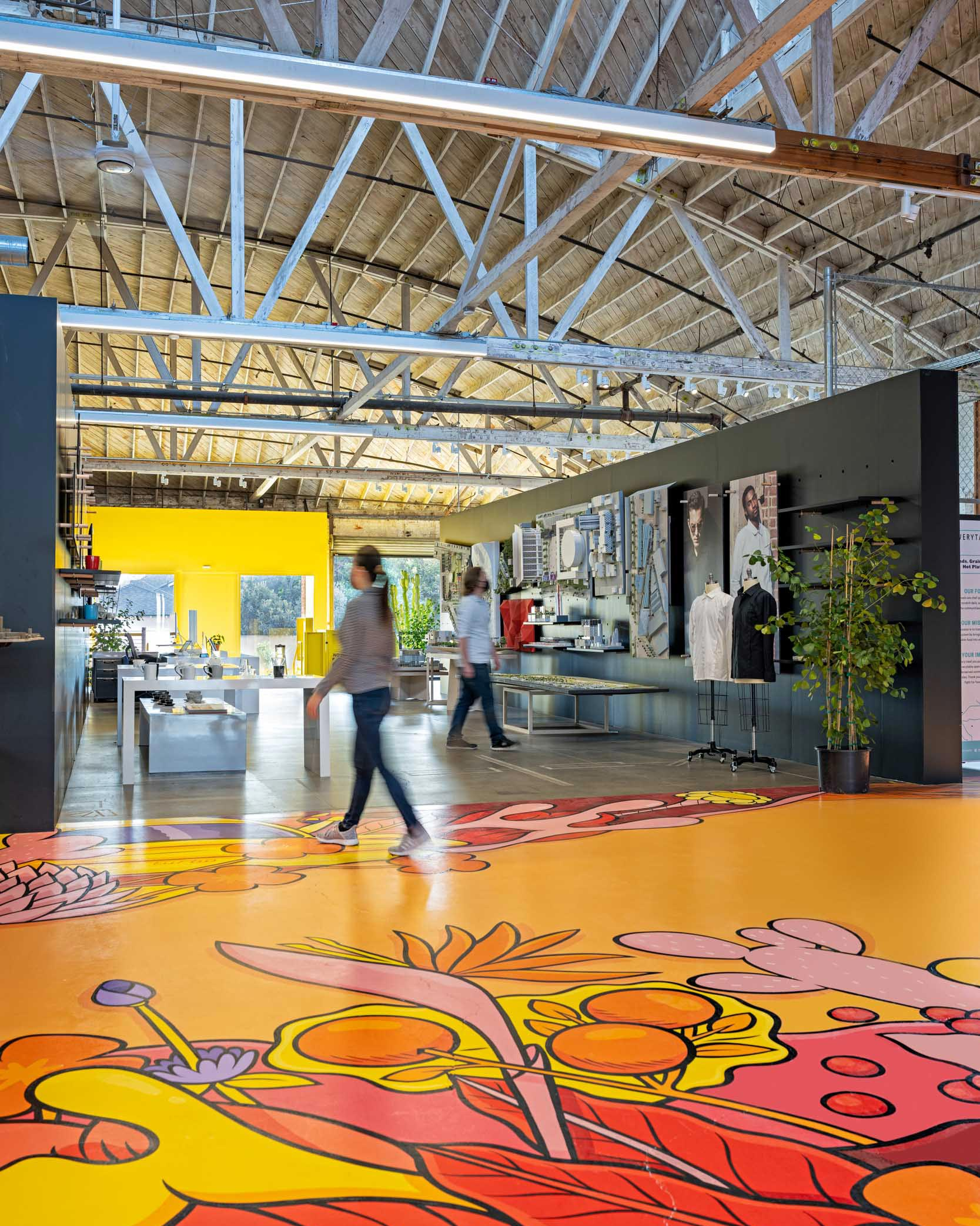 Interior shot of RIOS office with a red, pink, and yellow mural on the ground and industrial ceilings