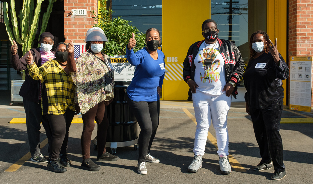 Los Angeles locals standing in front of the RIOS office wearing masks and giving a thumbs up