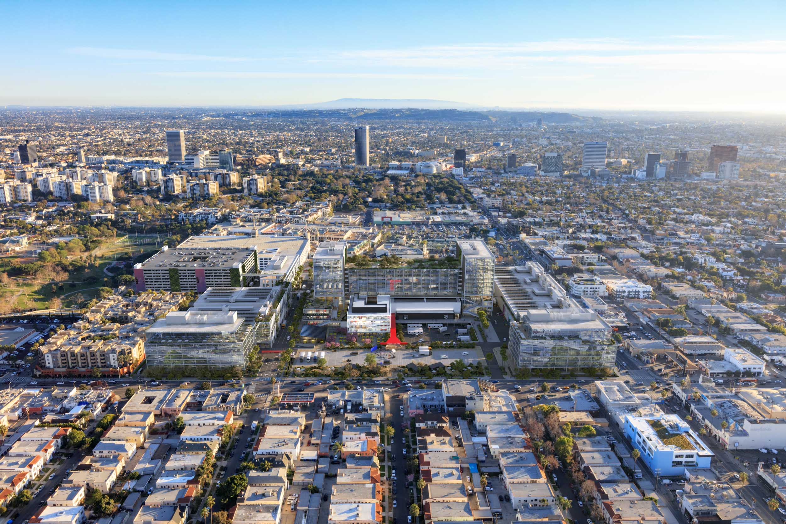 An aerial view of the proposed Television City 2050 with the surrounding city of Los Angeles and mountains in the background