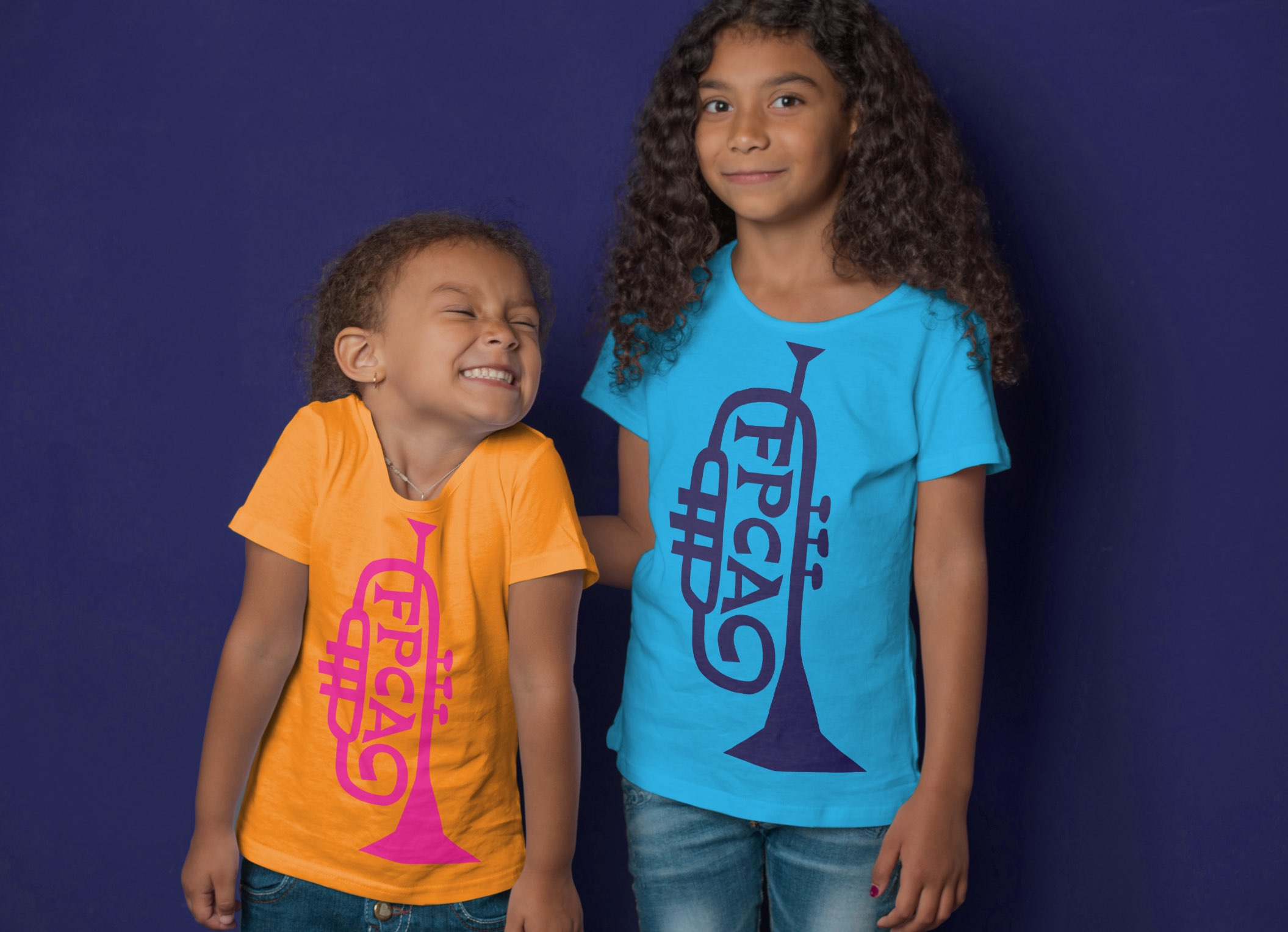 two young girls in brightly colored orange and blue tshirts with Fernando Pullum Center trumpet logo
