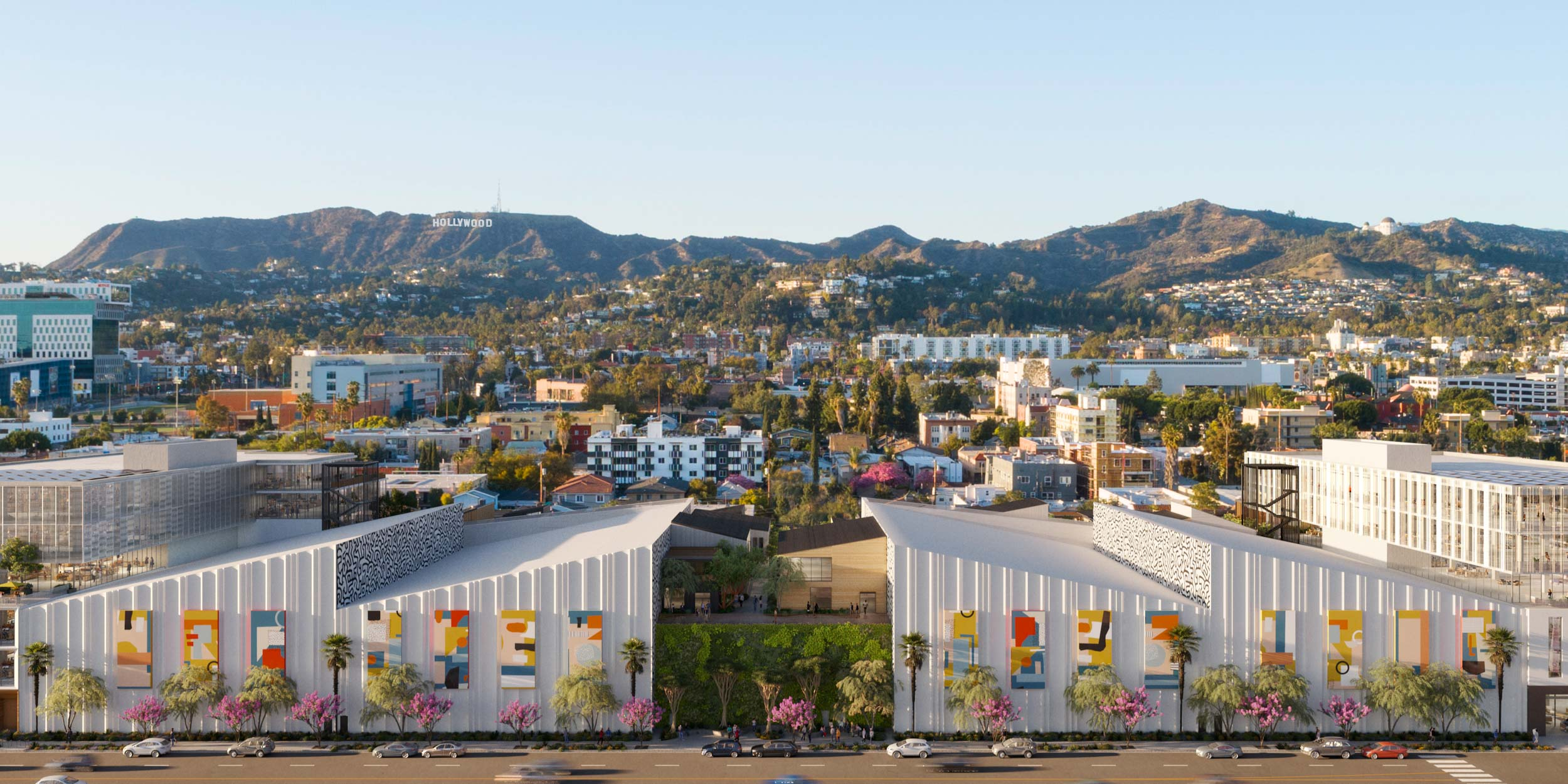 Side view of Echelon Studios building with angled ceilings, hanging art, and a view of the hollywood sign in the mountains behind